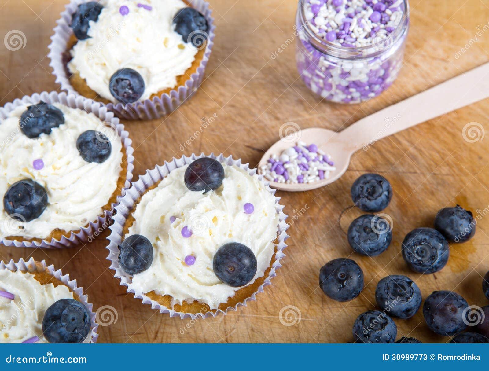 用_可口杯形蛋糕用蓝莓,奶油色和新鲜的莓果