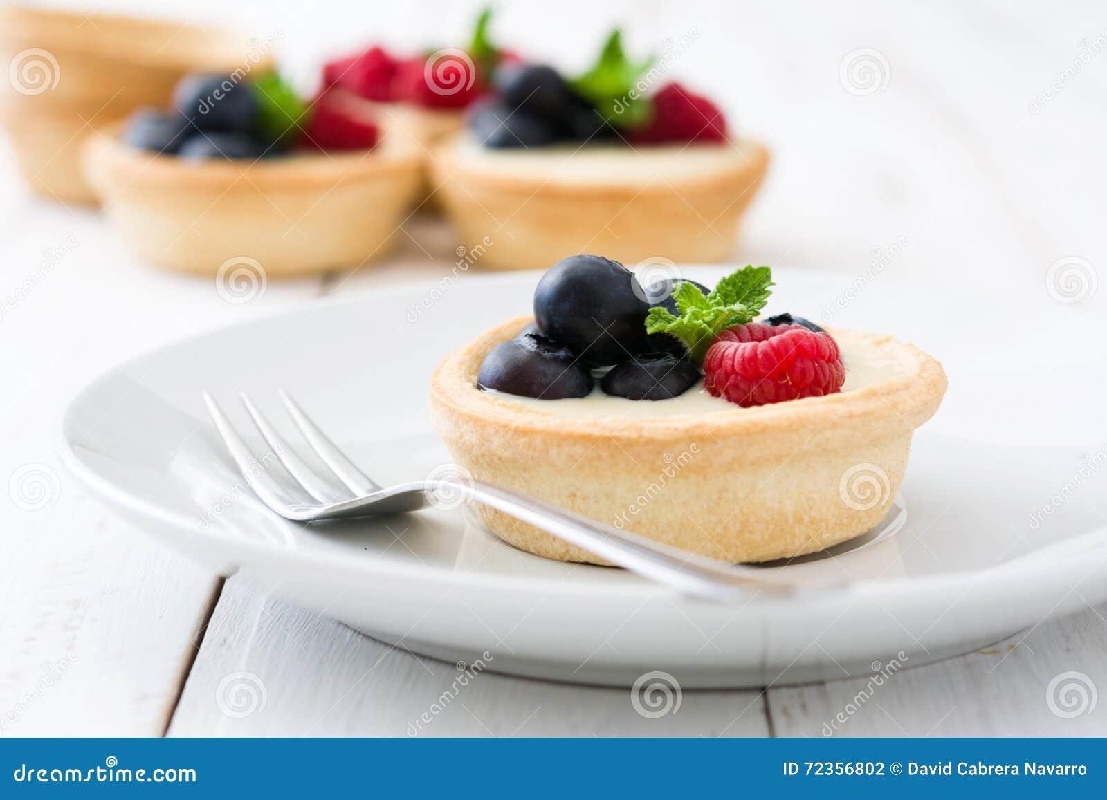 可口果子馅饼用莓和蓝莓在木背景