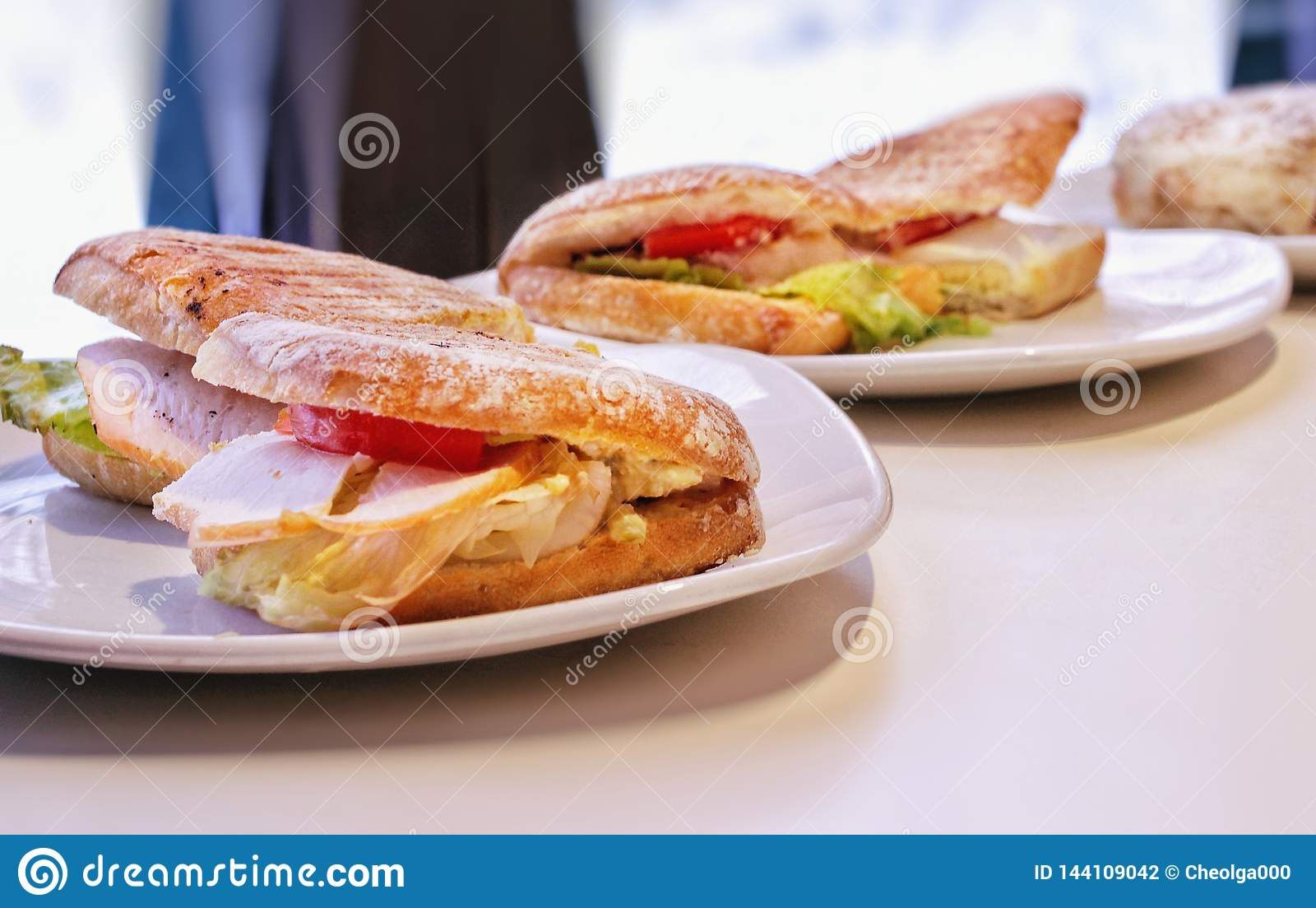 可口热的三明治用火鸡、鸡肉沙拉和蕃茄,在板材的裁减在桌上