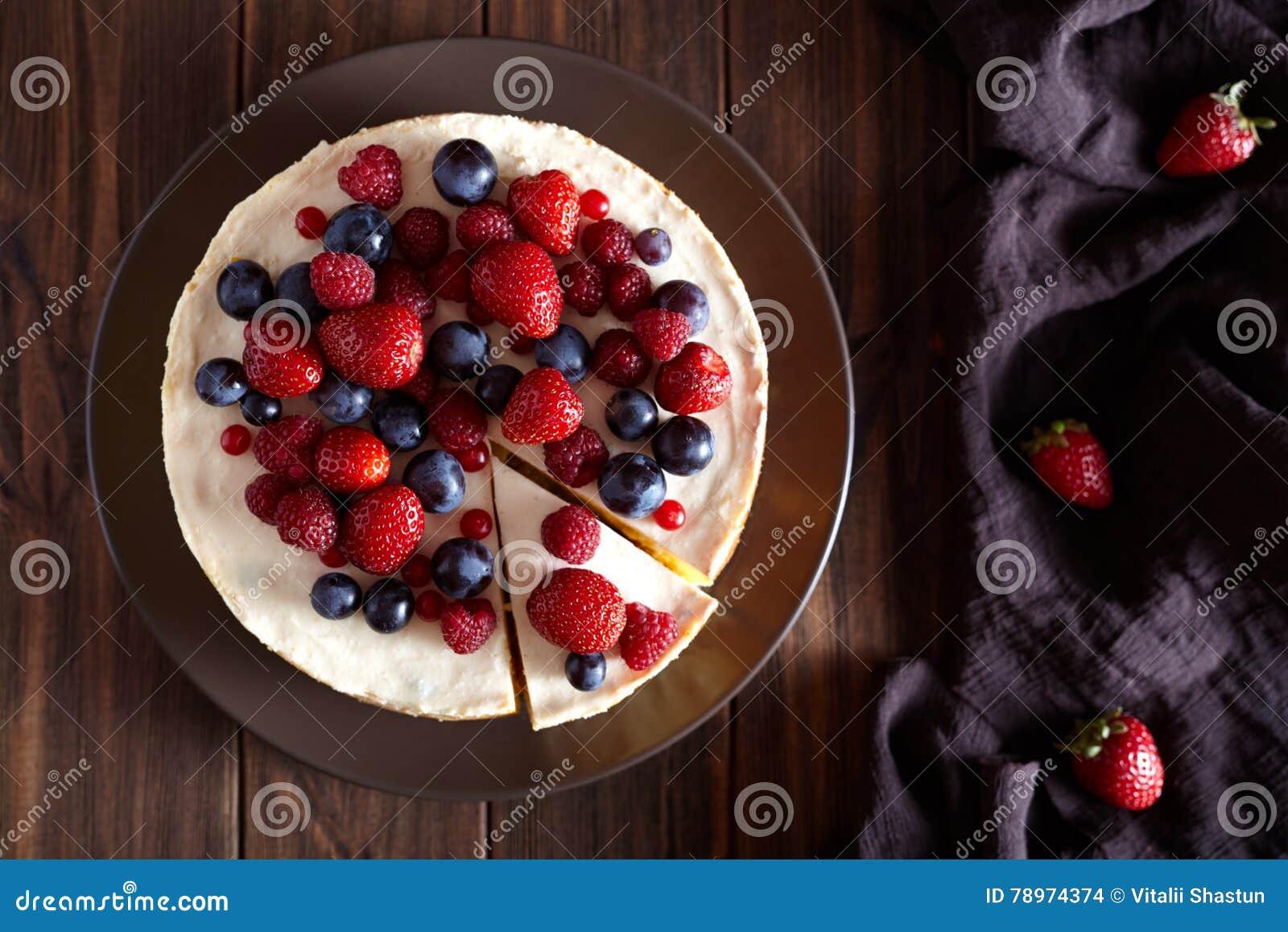 可口自创乳脂状的mascarpone纽约乳酪蛋糕用在黑暗的木桌上的莓果 顶面viev