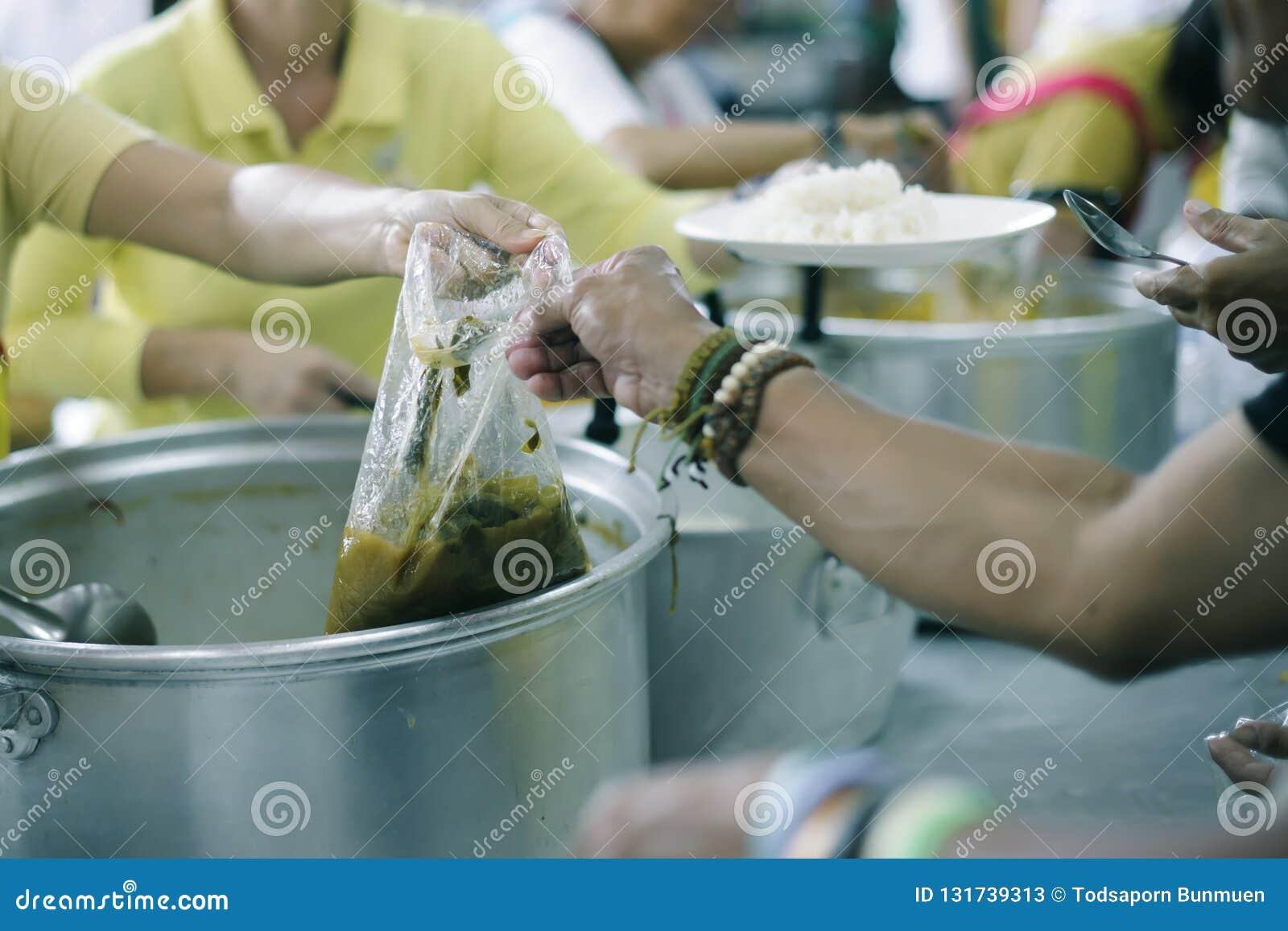 可怜的人民从捐款人接受捐赠的食物,展示相互分享在今天社会:帮助贫穷的概念
