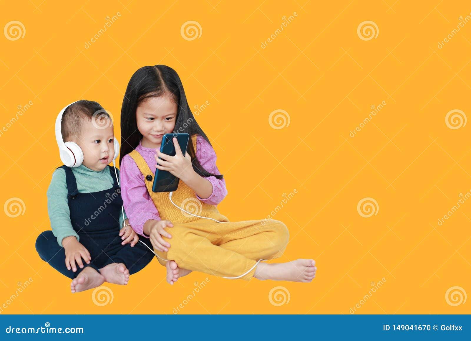 可爱的亚裔分享对的姐姐和弟弟由被隔绝的智能手机享受与耳机的听的音乐