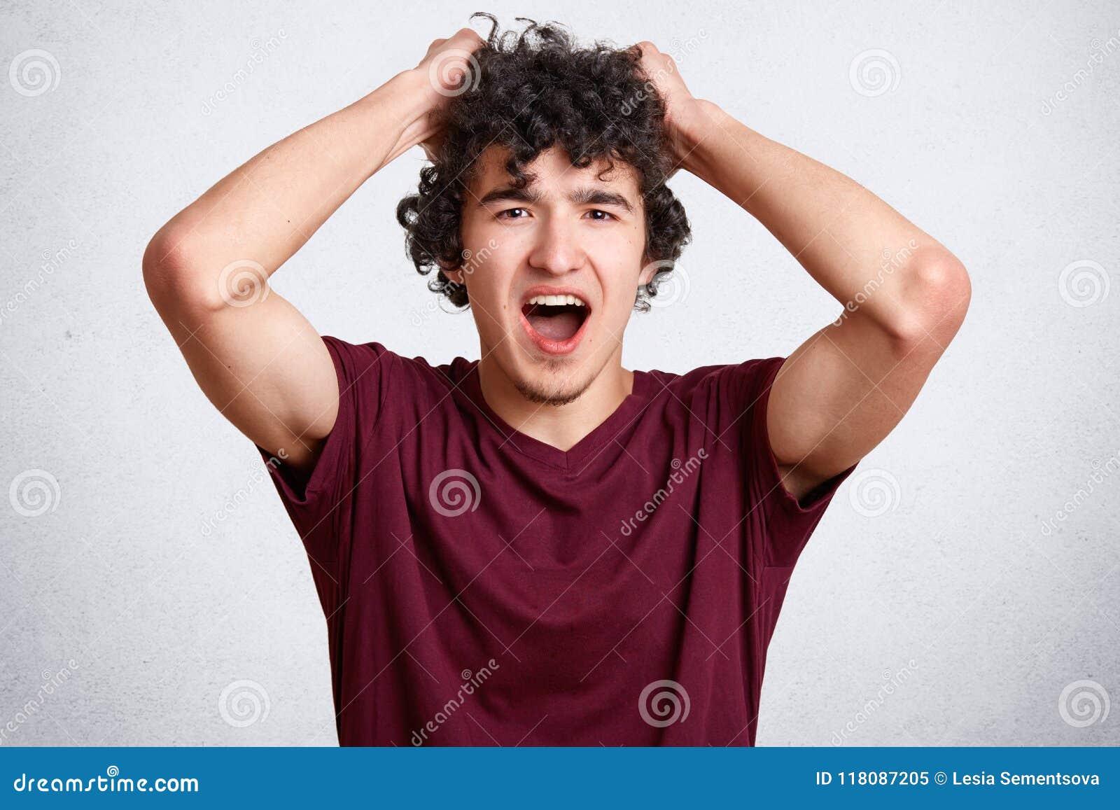 可爱的卷曲男性抓头并且响亮地惊叹,保留嘴宽打开,穿偶然T恤杉,摆在反对白色concr