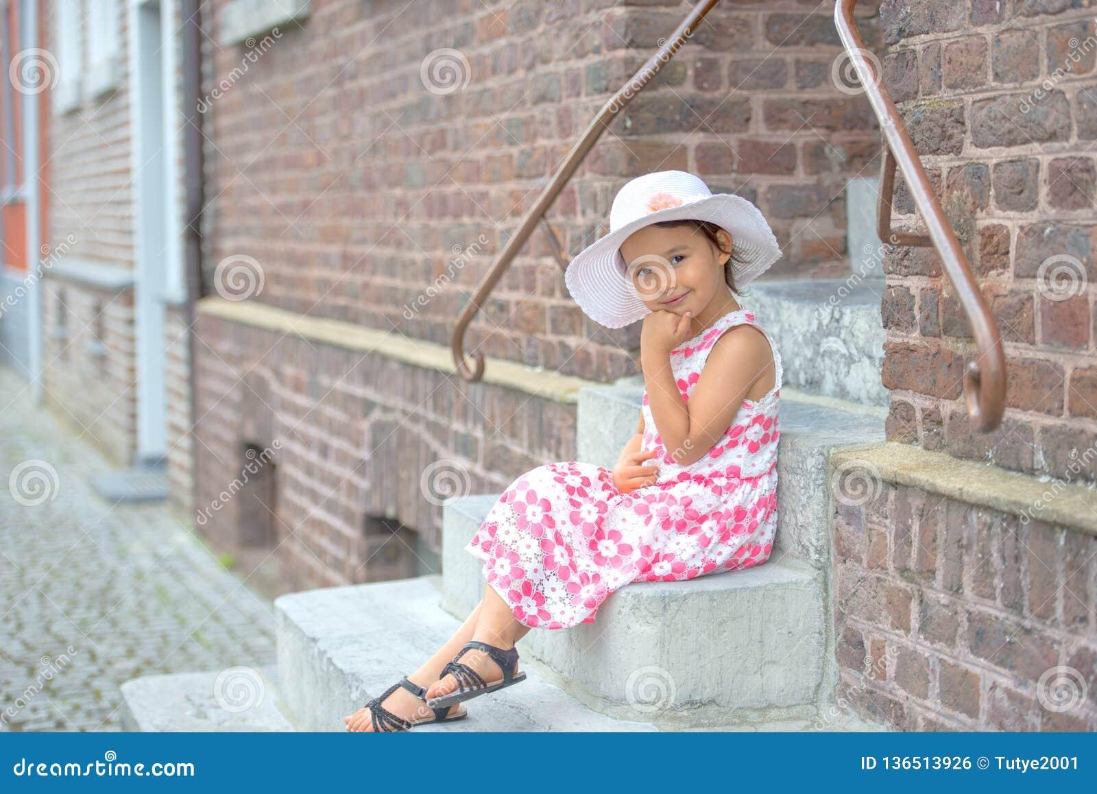 可爱的在台阶的女孩佩带的白色帽子开会