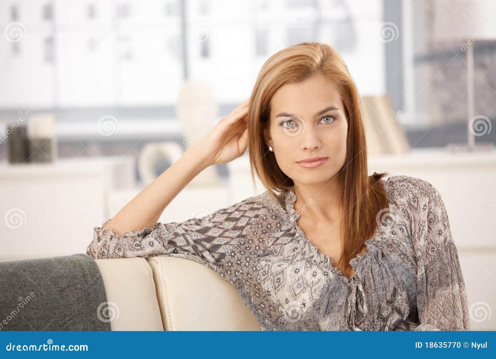 可爱的坐的沙发妇女