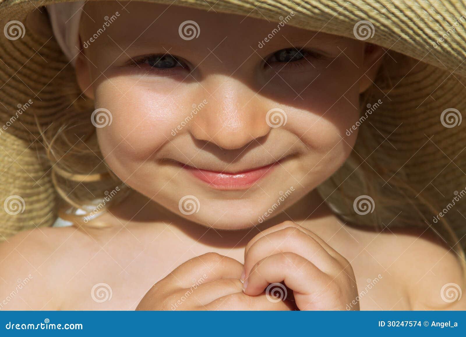 女婴面孔被日光照射了下面帽子