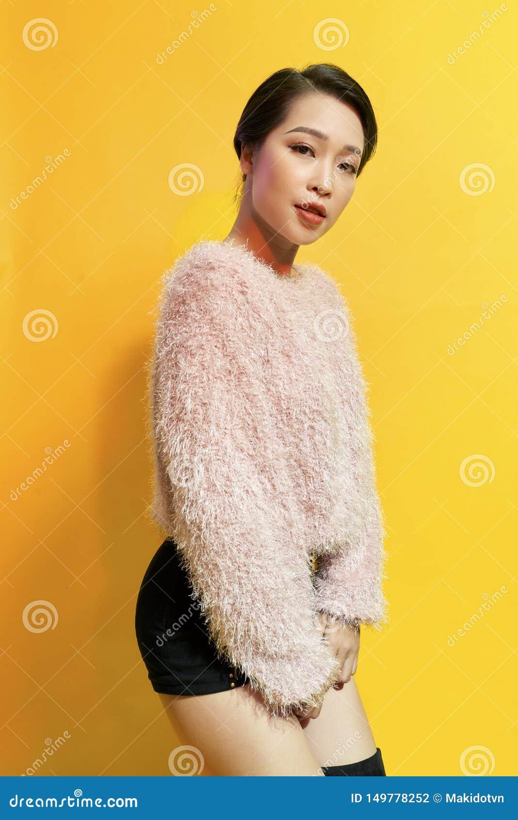 可爱的妇女表现出真实的正面情感在photoshoot期间用桃红色毛皮大衣 活跃迷人的女孩室内画象