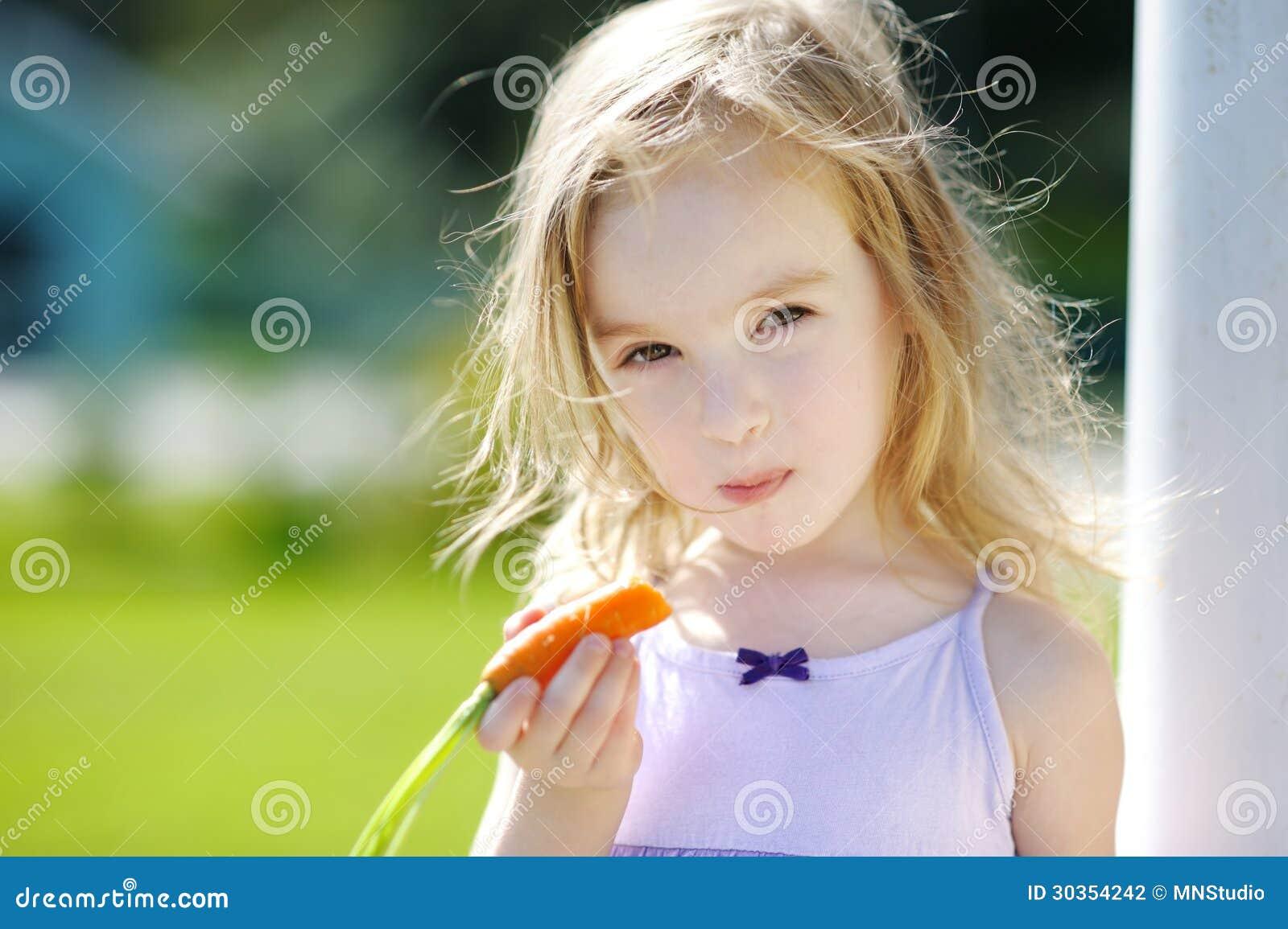 可爱的小女孩用红萝卜