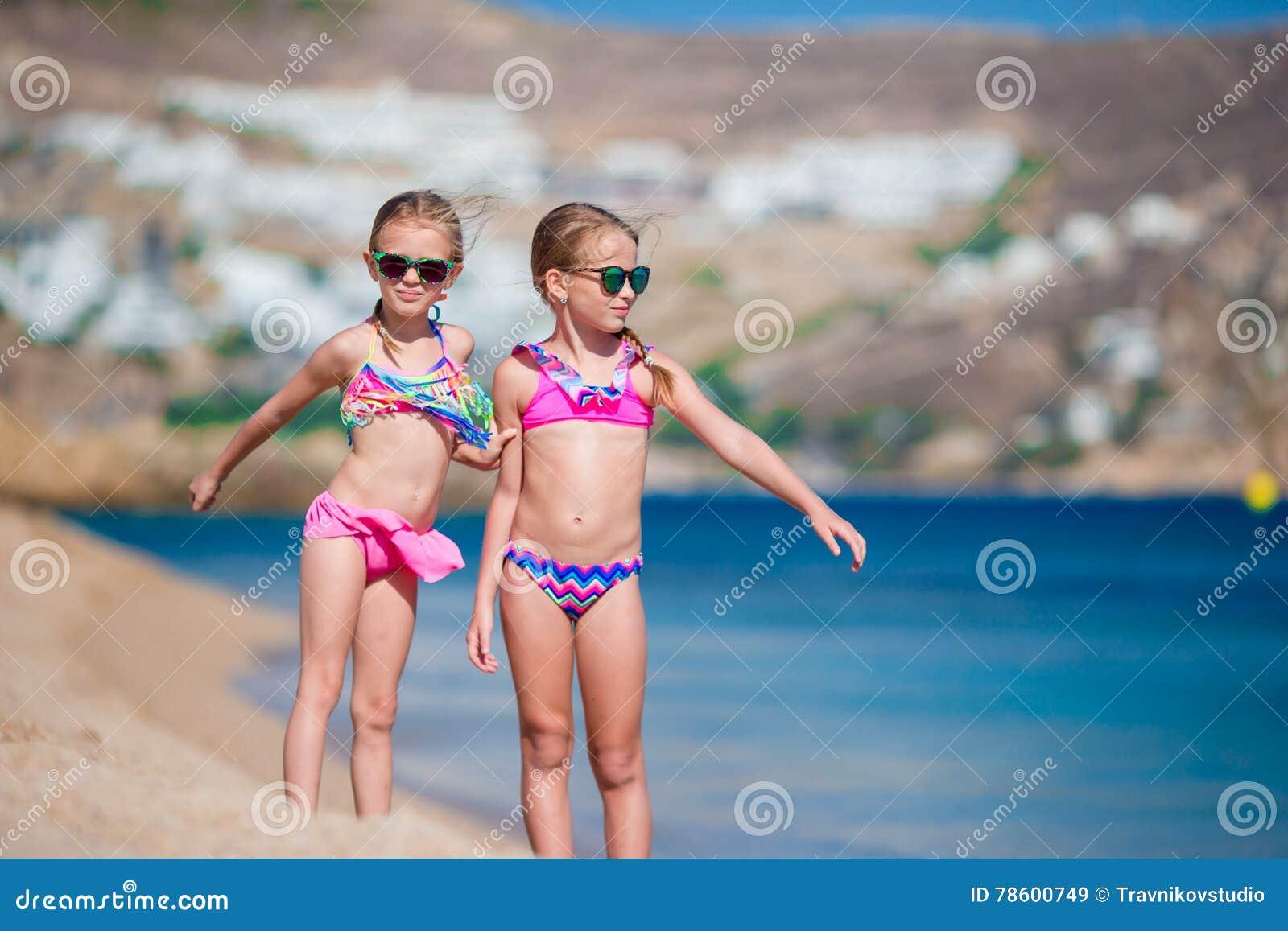 可爱的小女孩获得乐趣在海滩假期时 一起两个孩子希腊假期