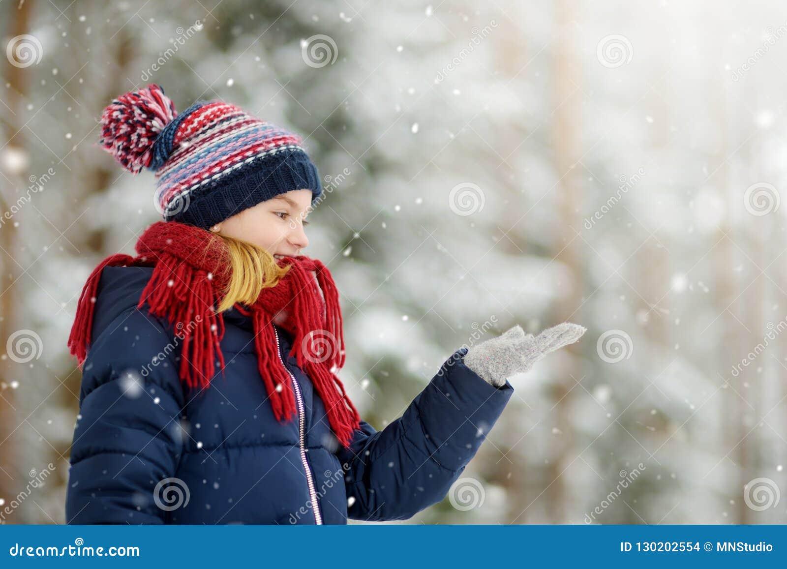 可爱的小女孩获得乐趣在美丽的冬天公园 使用在雪的逗人喜爱的孩子