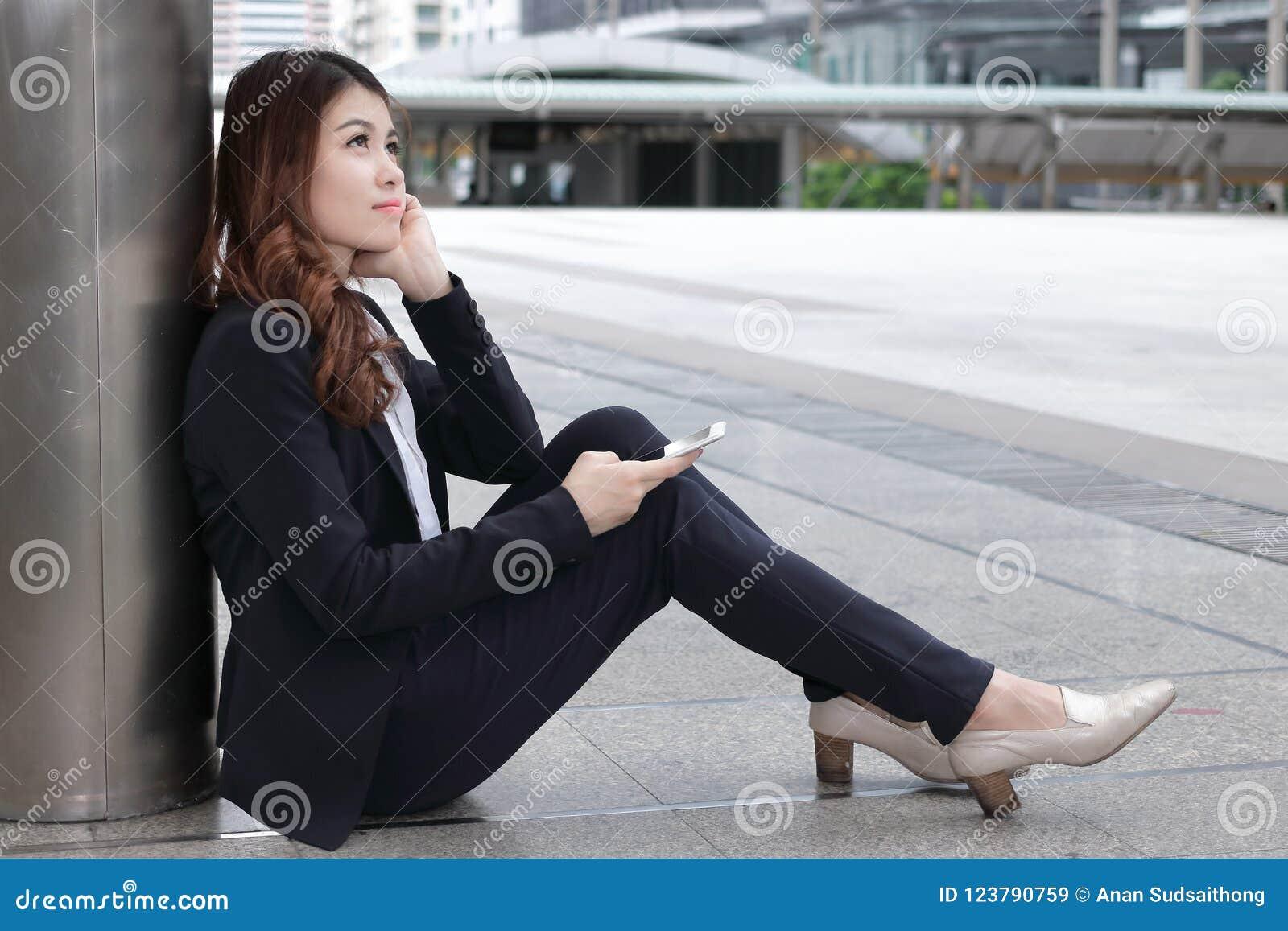 可爱的年轻亚裔女商人背面图坐地板和考虑她的工作的正式衣裳的在都市与警察