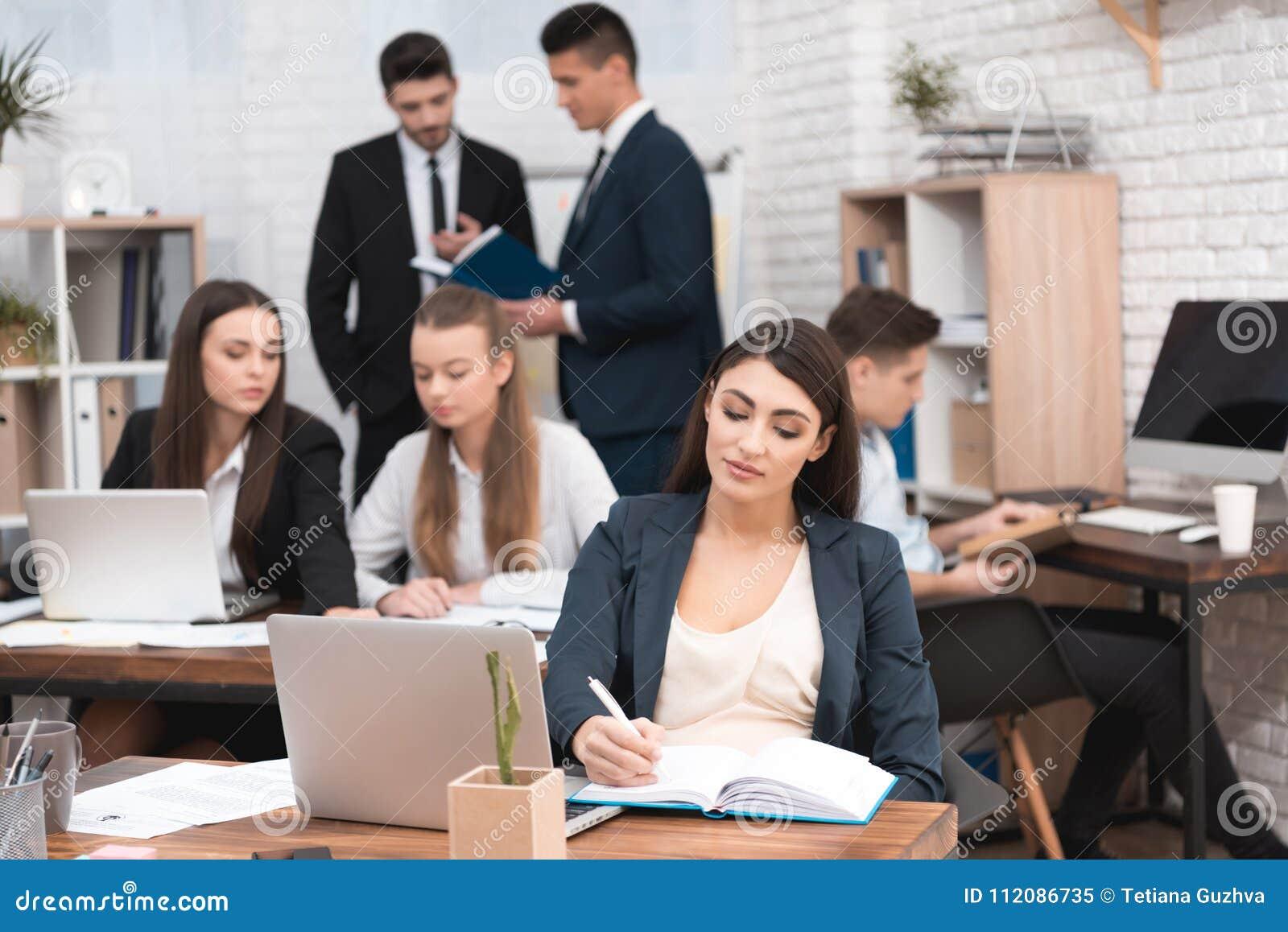 可爱的怀孕的女孩在有同事的办公室工作 工作区的怀孕的女实业家 产假
