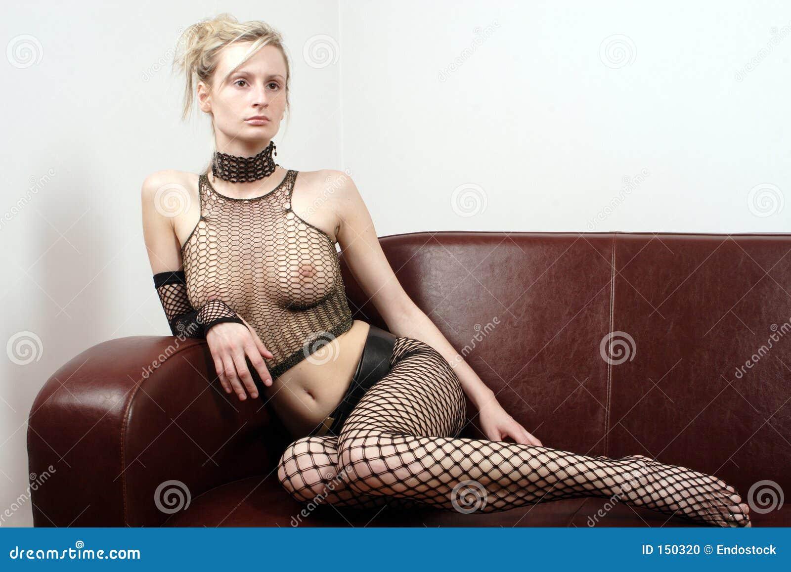 可爱的性感的坐的沙发妇女
