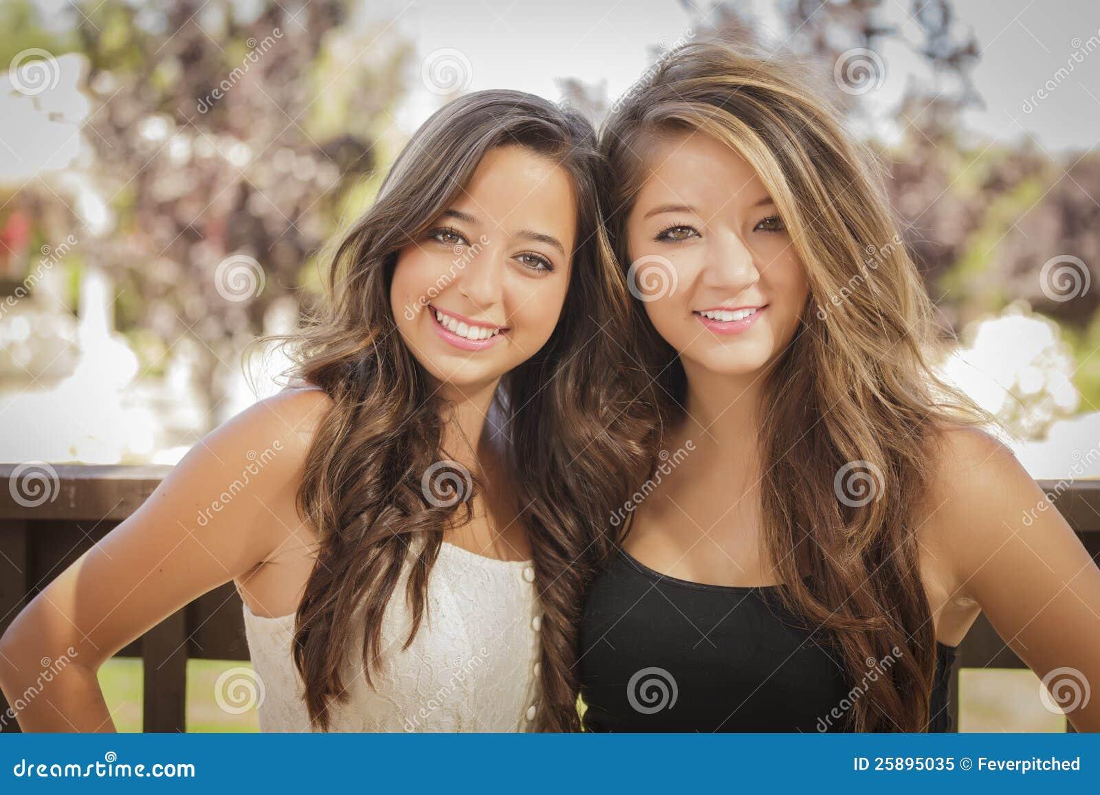二个可爱的混合的族种女朋友微笑得户外.图片