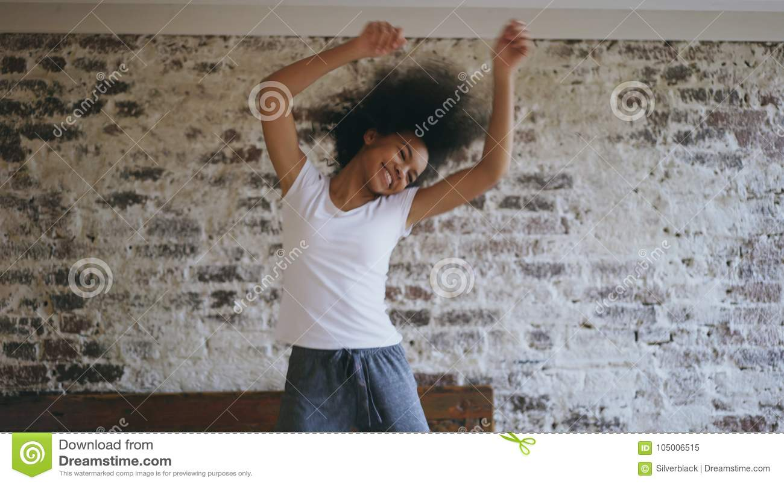 可爱的混合的族种年轻快乐的妇女获得在家跳舞在床附近的乐趣