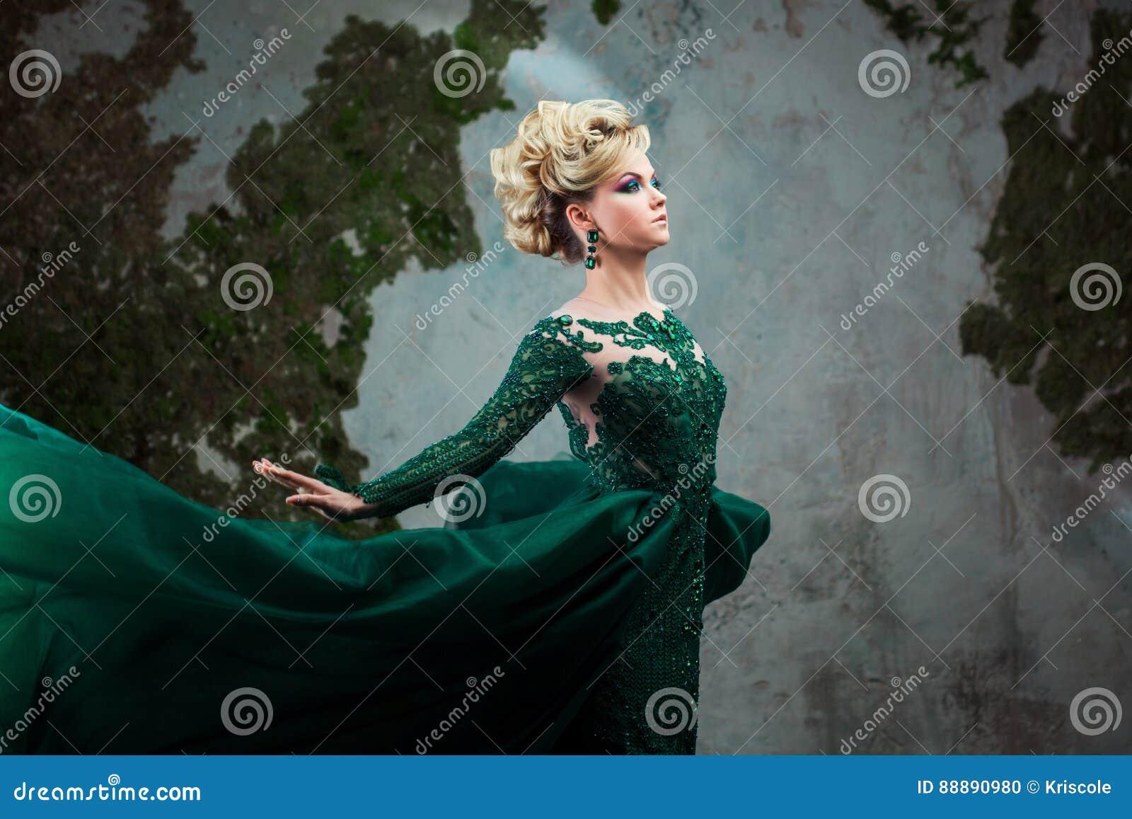 年轻可爱的白肤金发的妇女画象一件美丽的绿色礼服的 织地不很细背景,内部 豪华发型