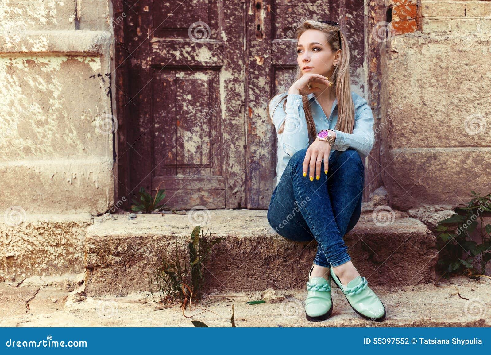 可爱的美丽的柔和的女孩在城市坐老大厦的步在牛仔裤和时尚鞋类的