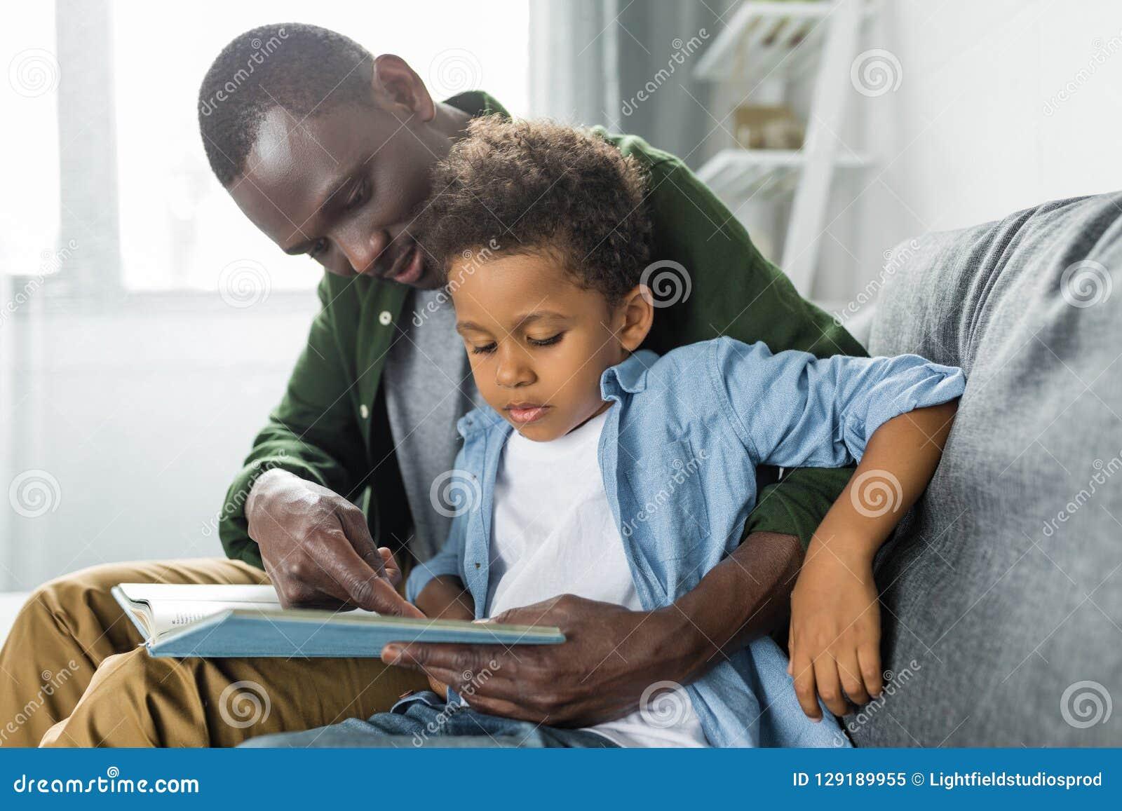 可爱的非裔美国人的父亲和儿子读书