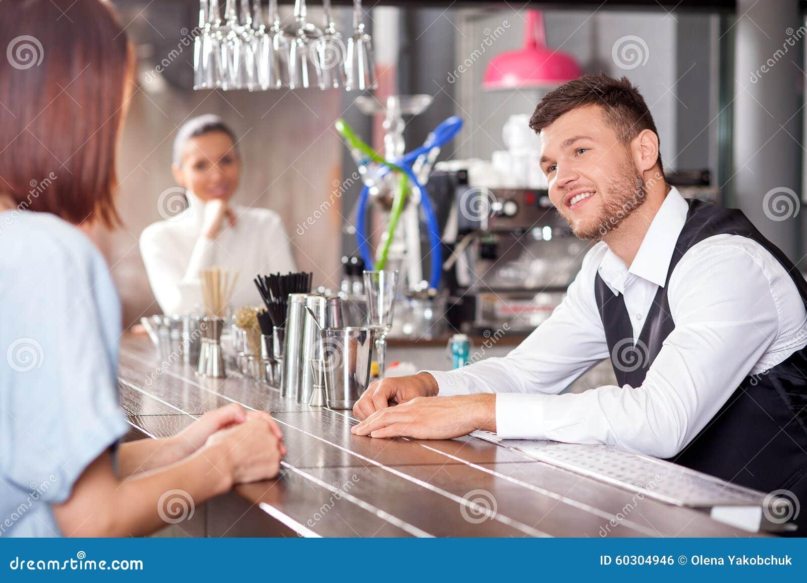 http://thumbs.dreamstime.com/z/woman-flirting-repairman-46285162.jpg_快乐的侍酒者站立在柜台并且与妇女谈话 他看夫人flirtingly和微笑