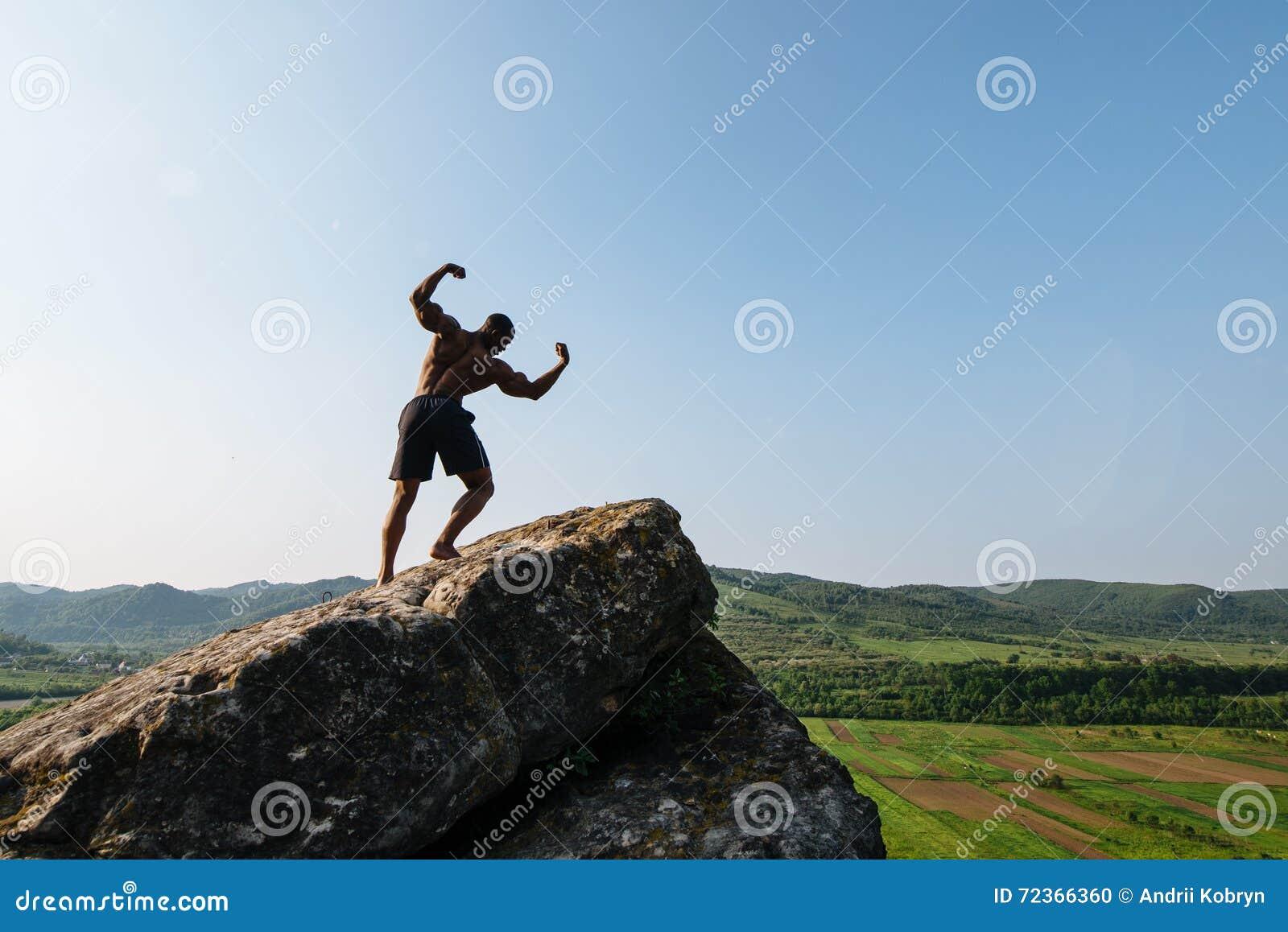 可爱的年轻非裔美国人的运动人画象有赤裸躯干的在岩石 背景绿色本质