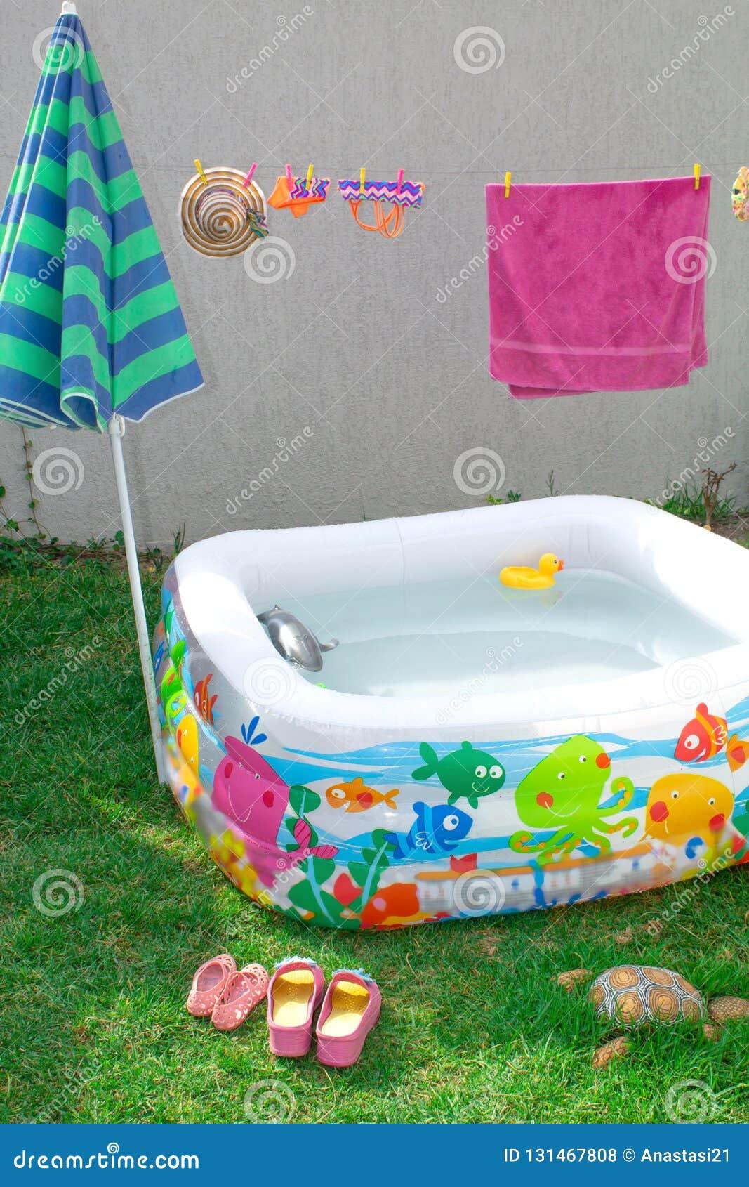 可膨胀的水池在庭院里,有伞的