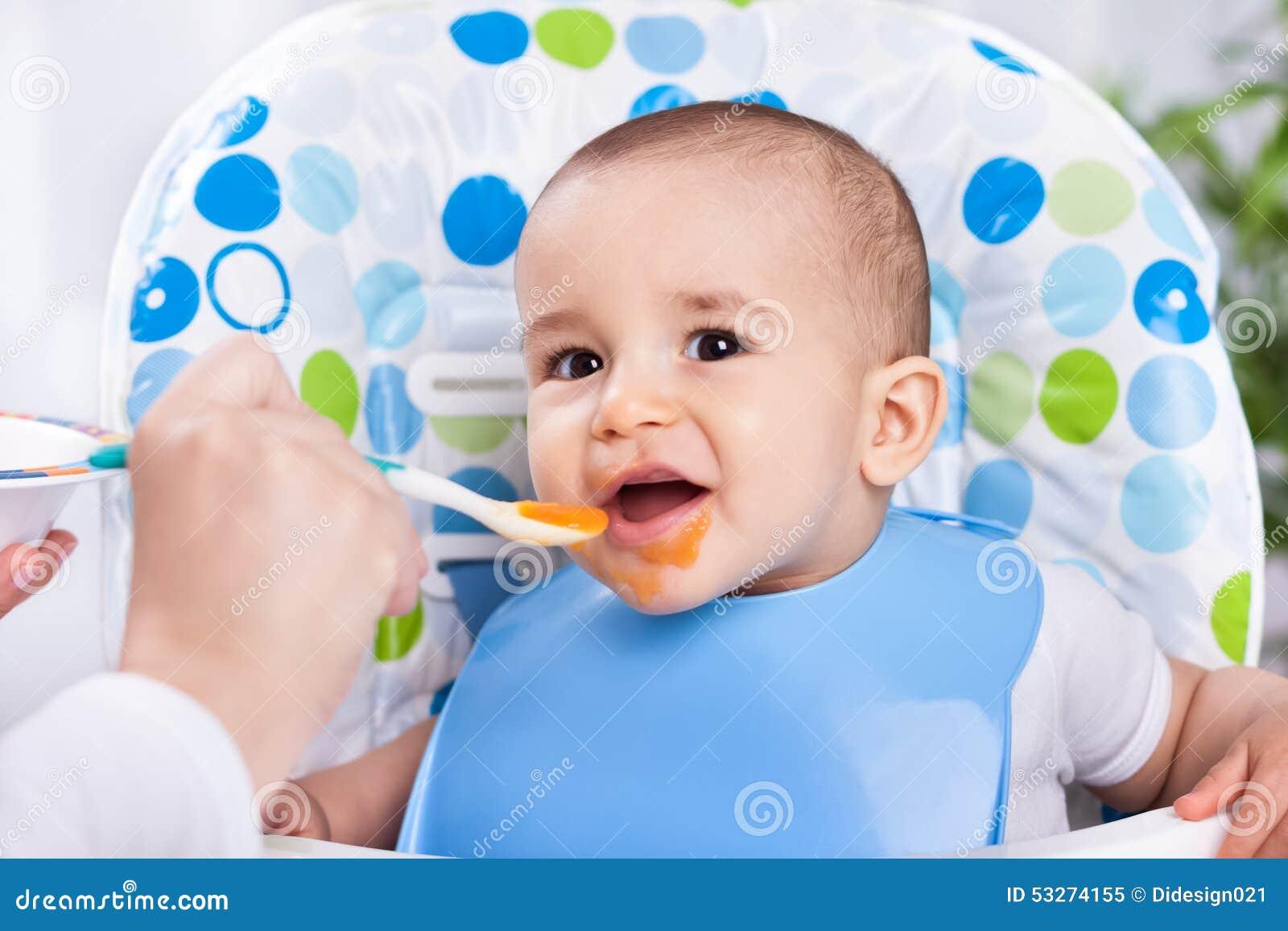 吃与匙子的微笑的愉快的婴孩