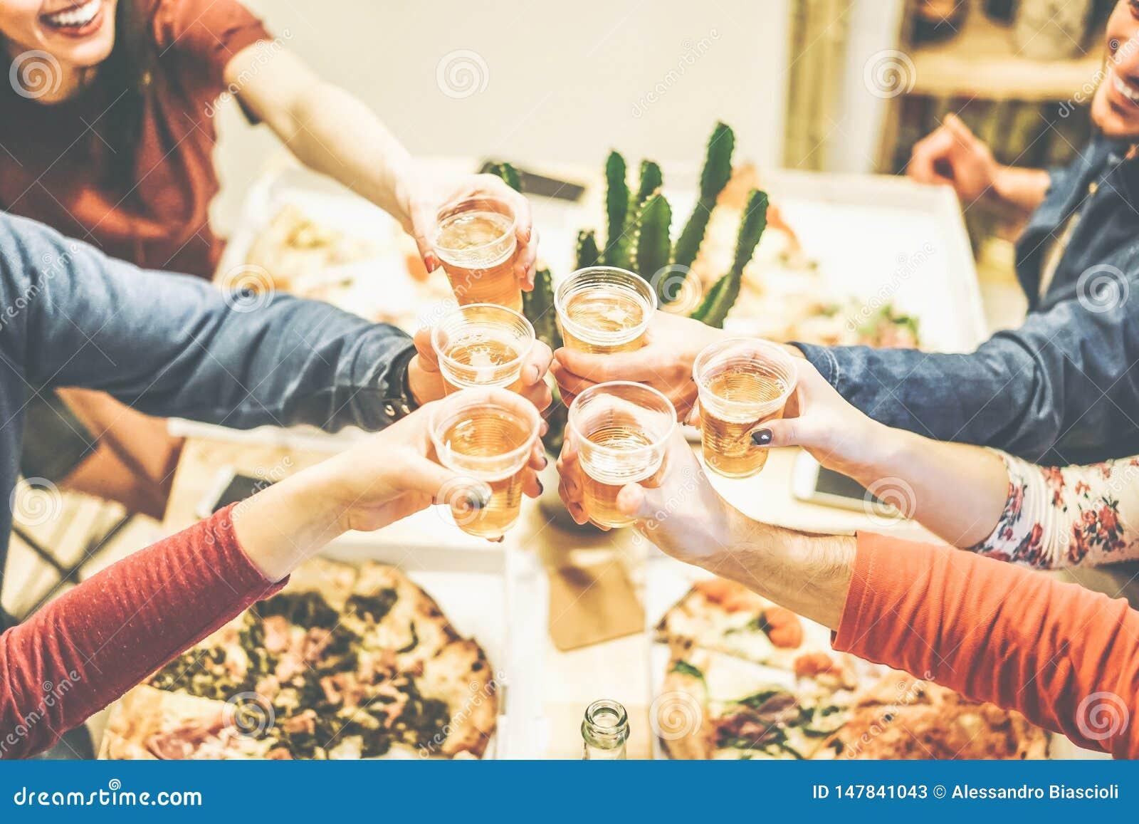 吃享受晚餐的小组朋友敬酒用啤酒和在家拿走愉快的人民饮用的啤酒比萨-欢呼
