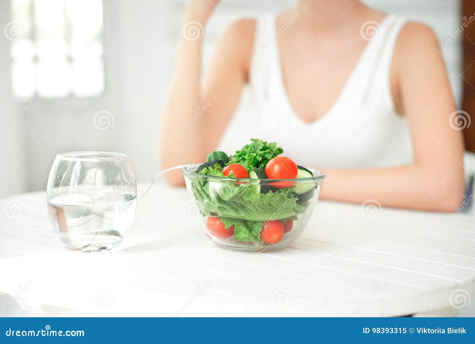 吃健康沙拉的美丽的适合妇女