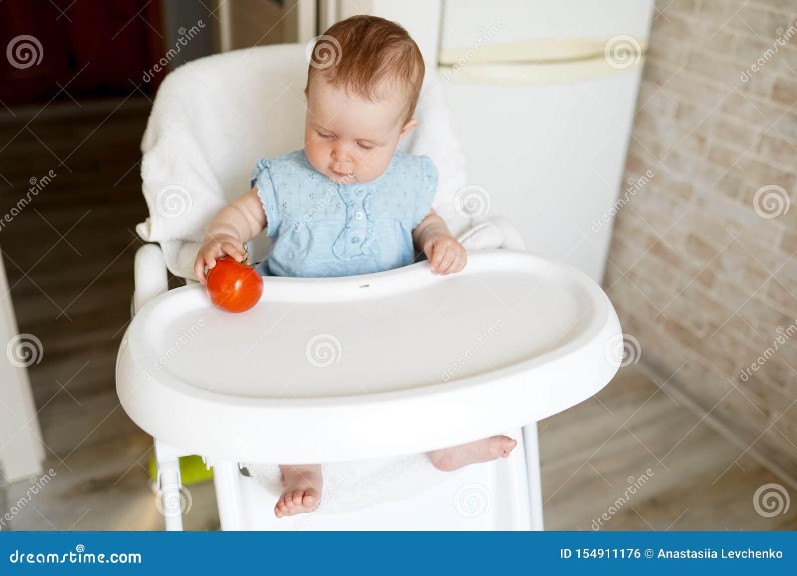 吃健康食品的逗人喜爱的儿童女孩在幼儿园 椅子的婴孩