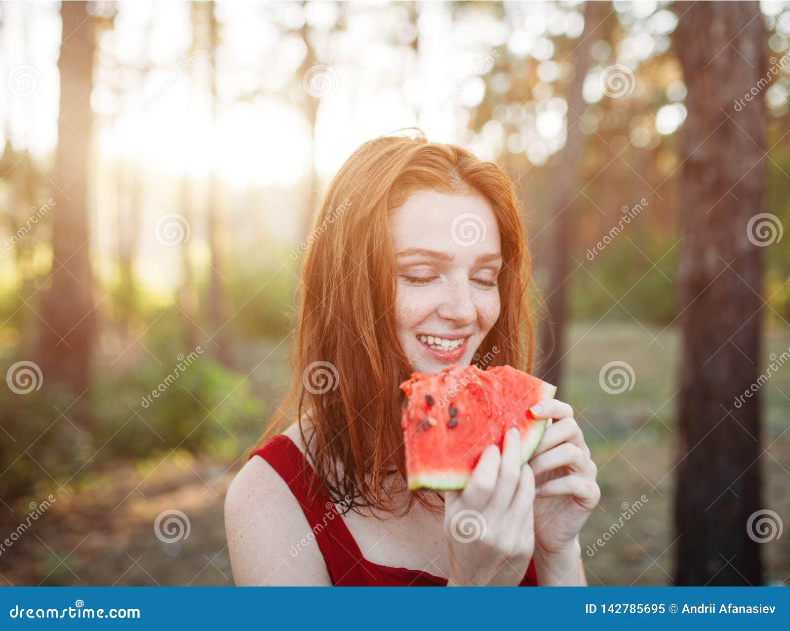 吃在自然的愉快的年轻女人西瓜 青年生活方式 幸福,喜悦,假日,海滩,夏天概念