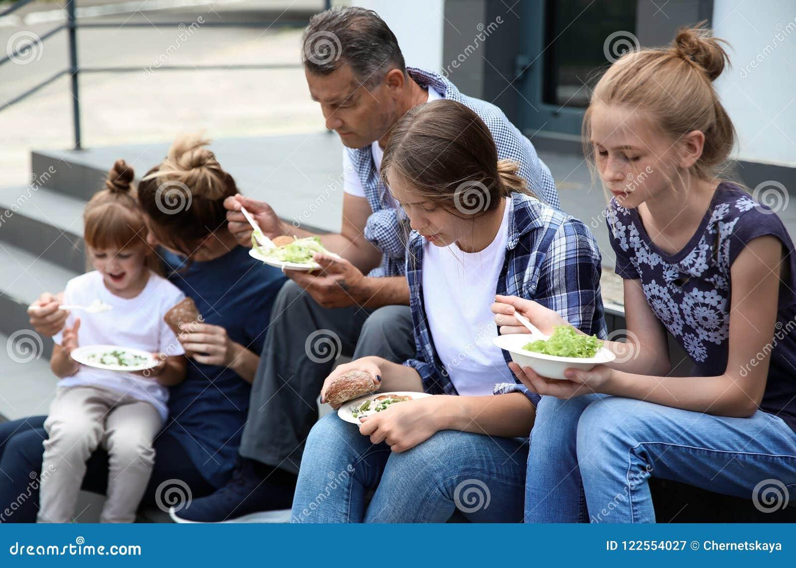 吃捐赠的食物的可怜的人民