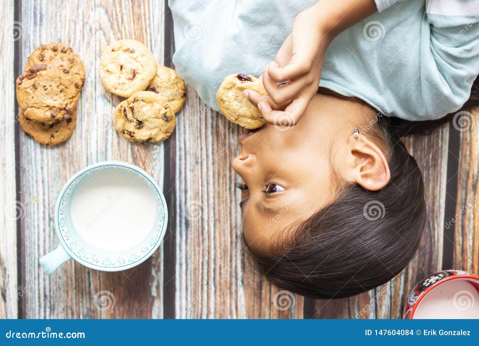 吃曲奇饼用牛奶的逗人喜爱的女孩