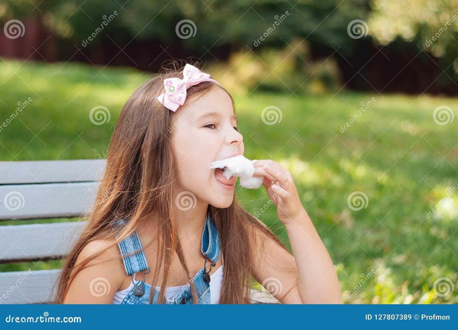 吃棉花糖的小女孩坐一条长凳在公园夏天