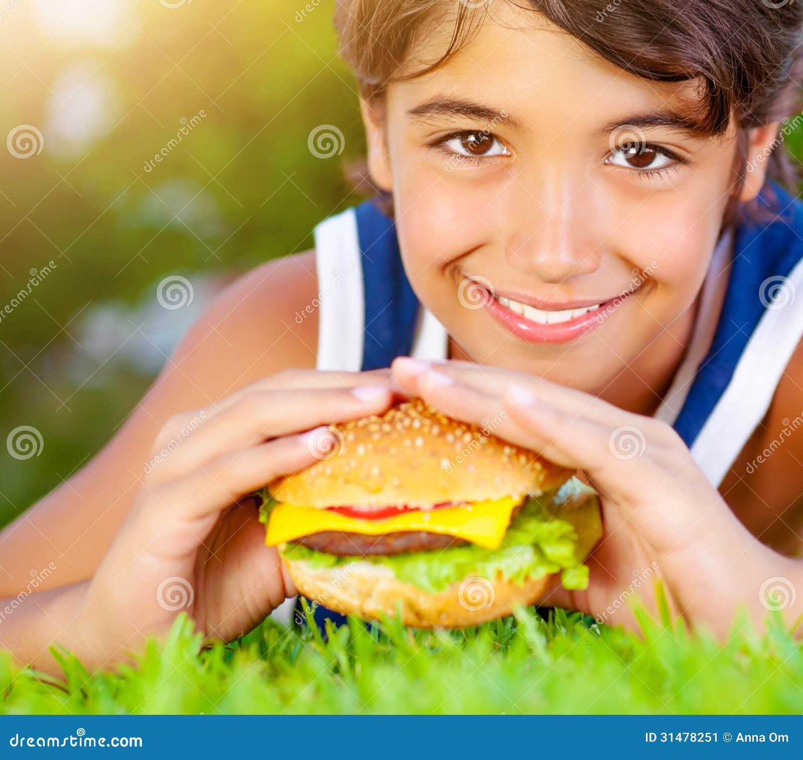 吃汉堡的愉快的男孩