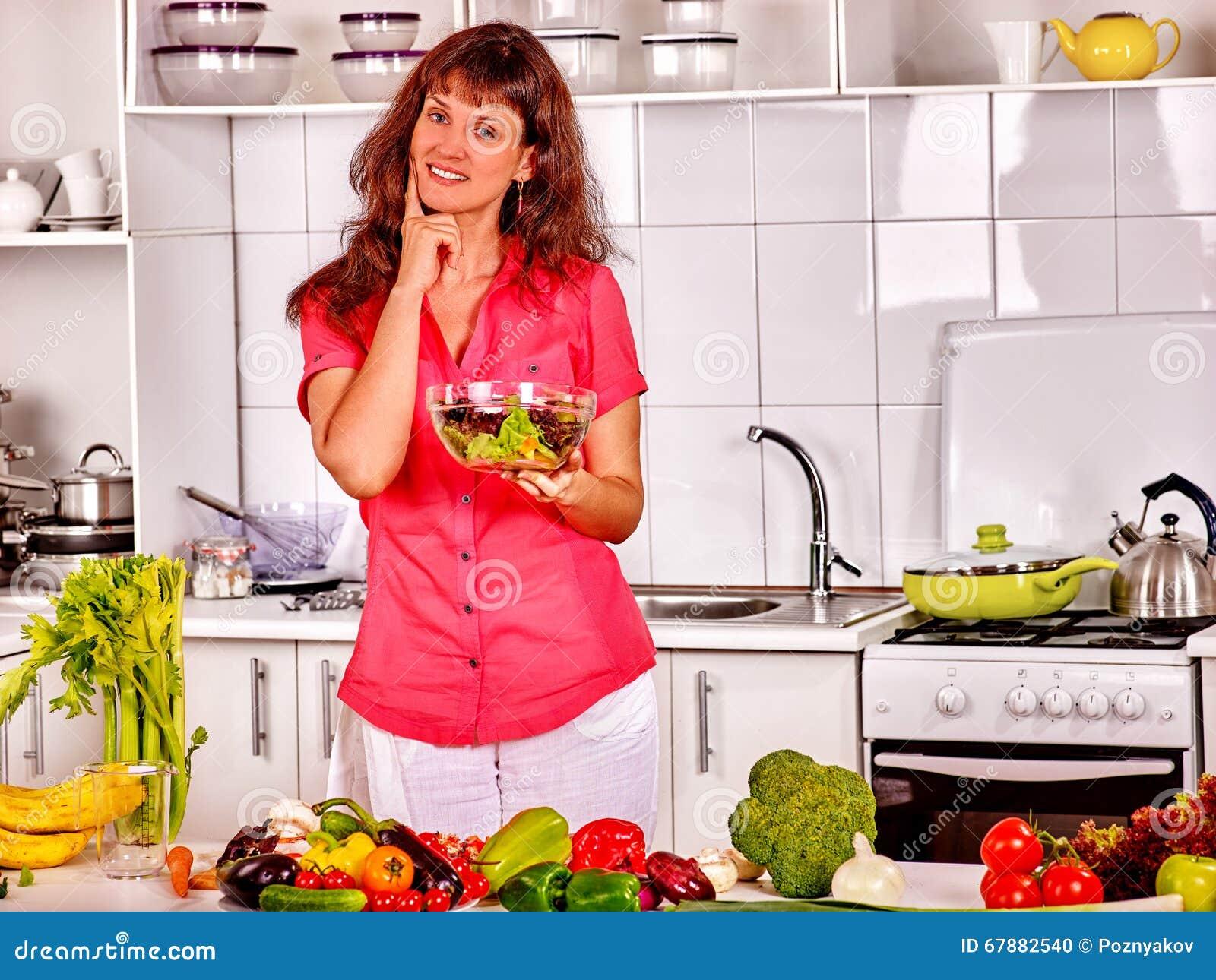 吃沙拉的妇女在厨房