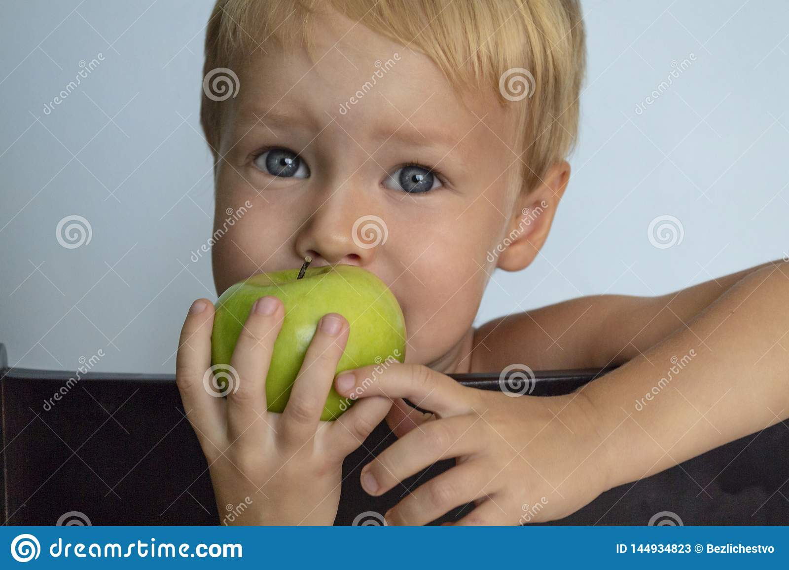 吃绿色苹果计算机的逗人喜爱的欧洲白肤金发的男孩 r