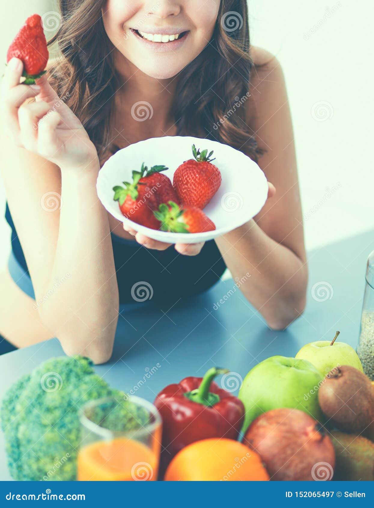 吃草莓的微笑的妇女 女性面孔画象的关闭