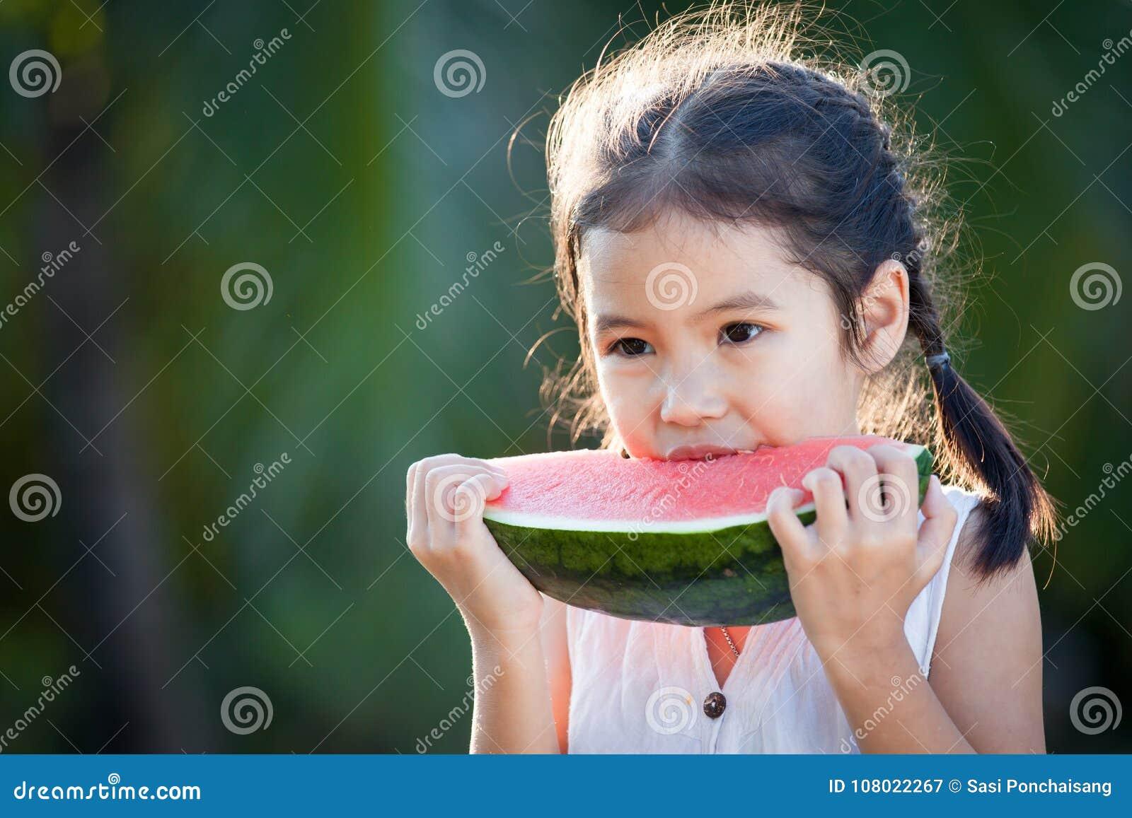 吃西瓜新鲜水果的逗人喜爱的亚裔小孩女孩