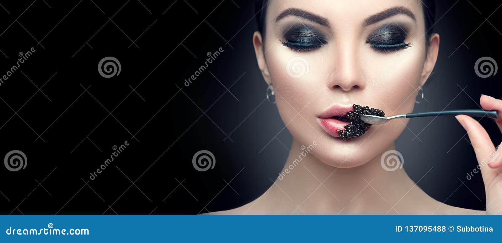 吃黑鱼子酱的美丽的时装模特儿妇女 秀丽女孩用在她的嘴唇的鱼子酱