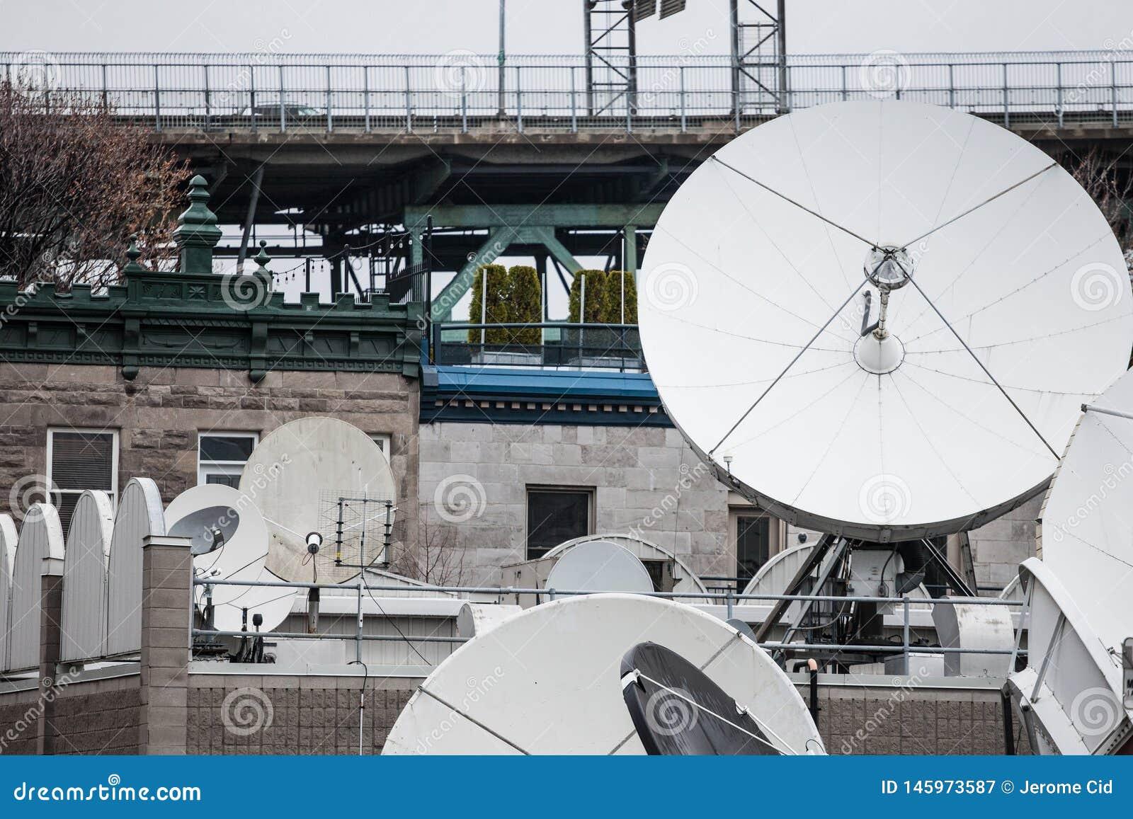 各种各样的卫星盘和放射器在一名媒介电视和无线电播报员的技术插孔在蒙特利尔的郊区,