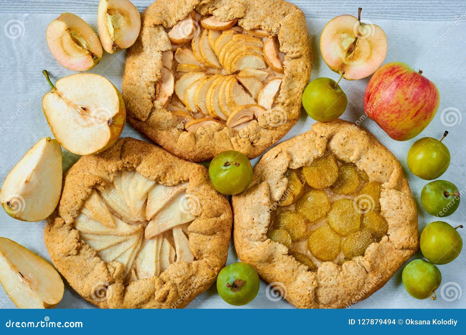 各种各样的果子馅饼- galette用新鲜的苹果、李子和梨在灰色具体桌上 素食健康秋天点心