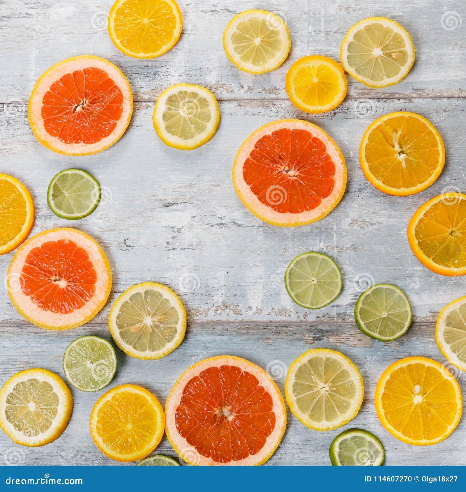 各种各样的柑橘水果框架和延命菊在白色背景,顶视图开花