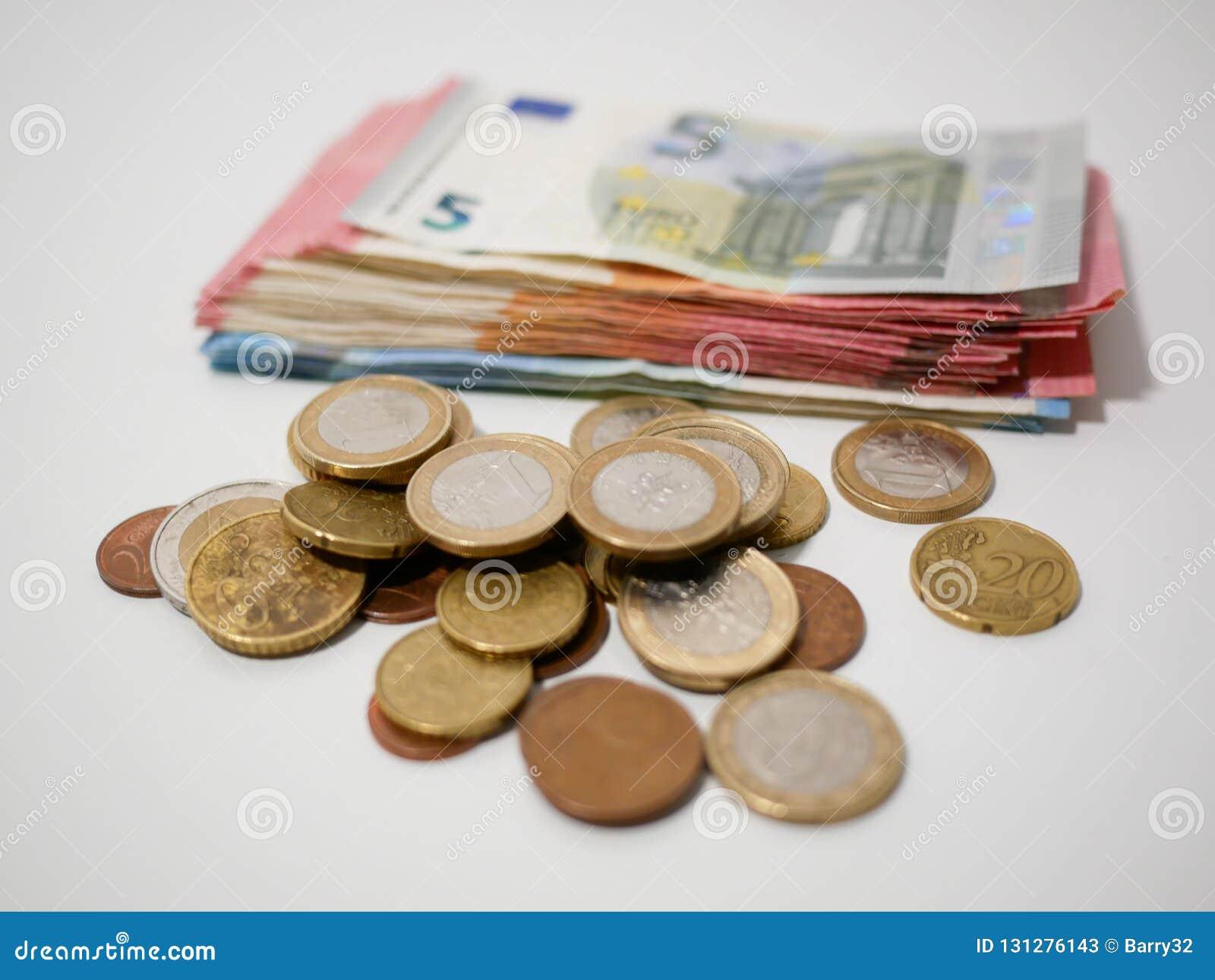 各种各样的欧元硬币和钞票在一张白色书桌上 各种各样的衡量单位纸币和硬币