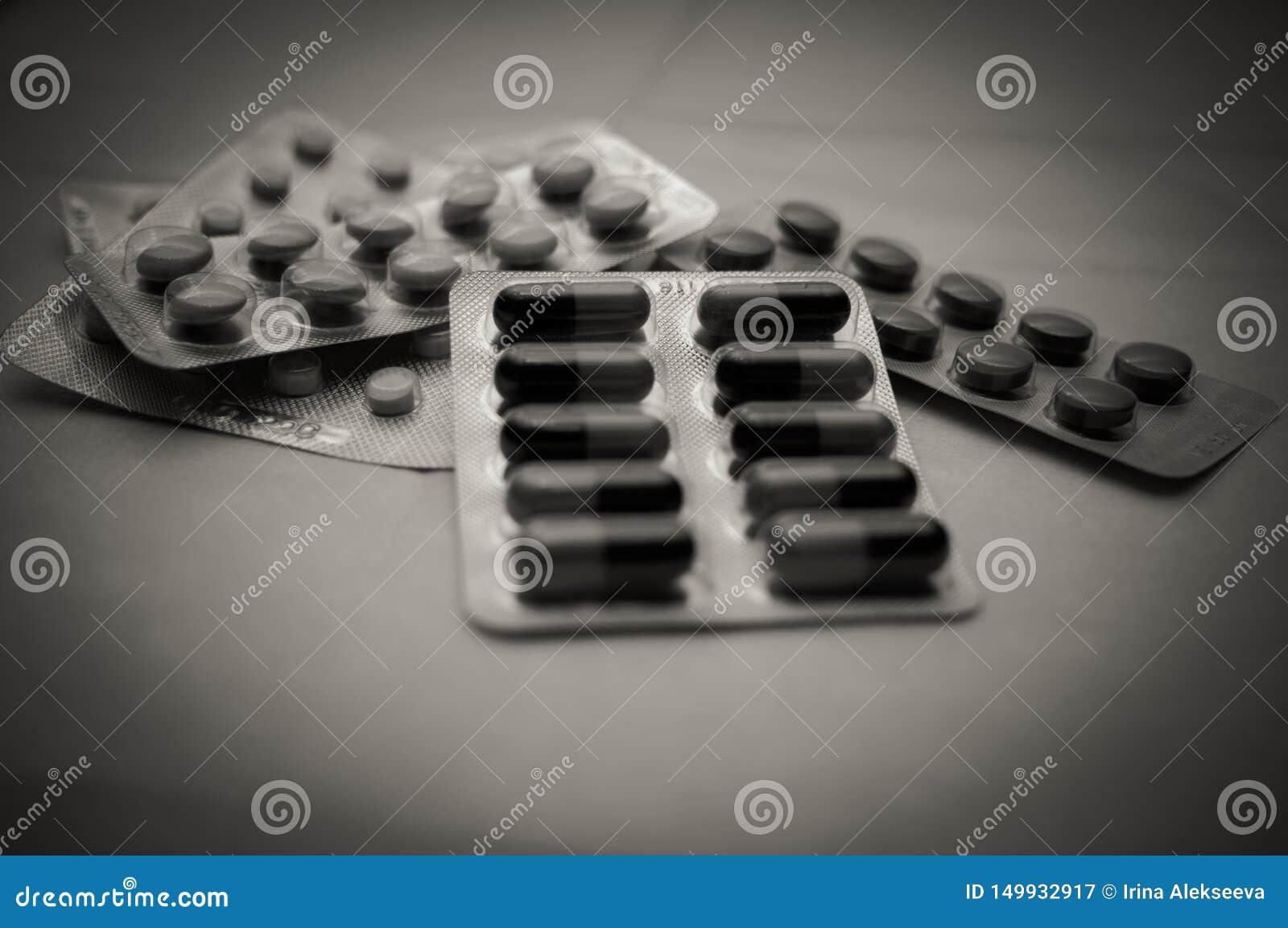各种各样的药片和胶囊在水泡特写镜头,软的焦点 与渐晕的黑白照片 害处的概念从