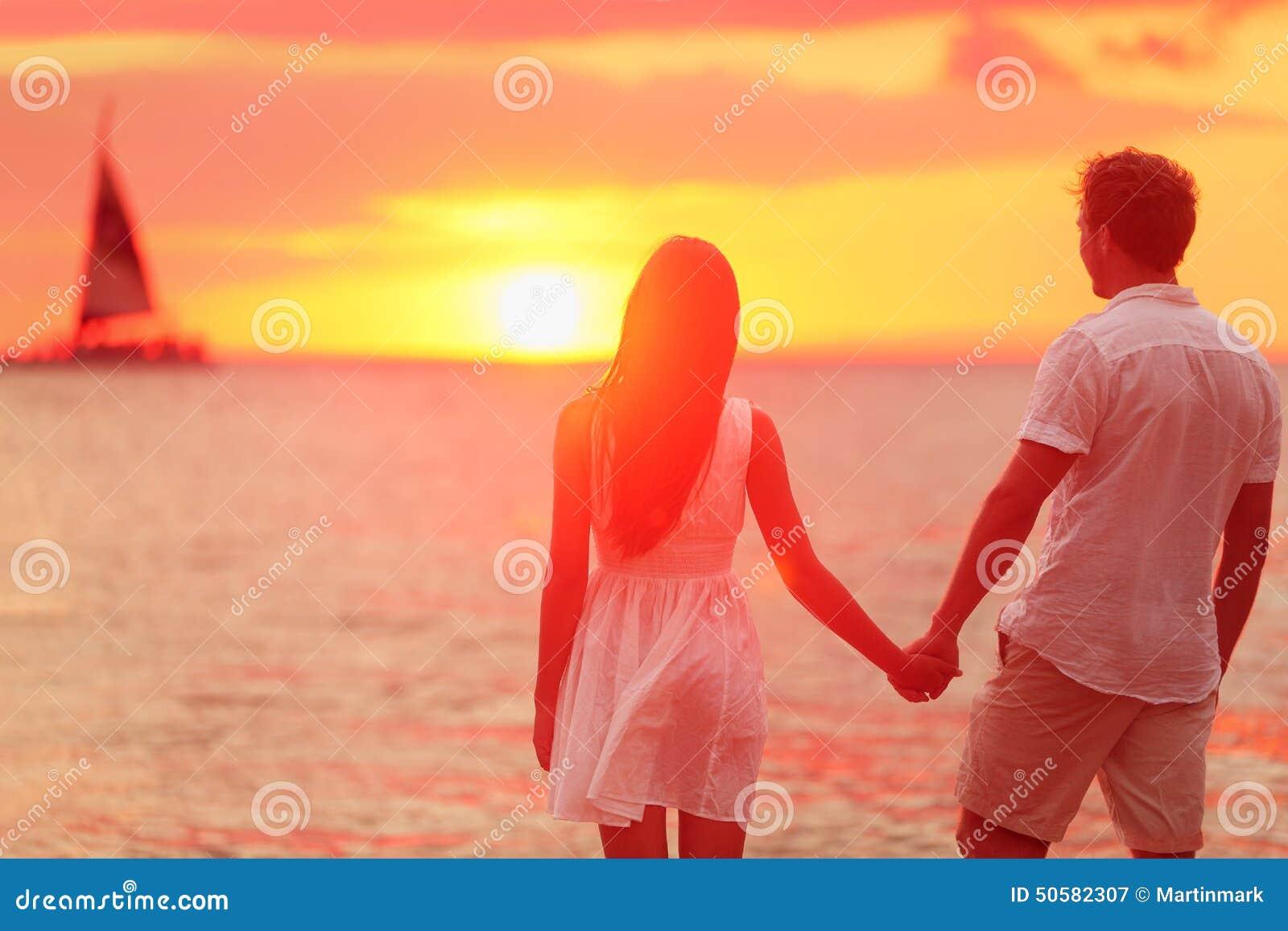 结合在一起使手的夫妇在海滩日落