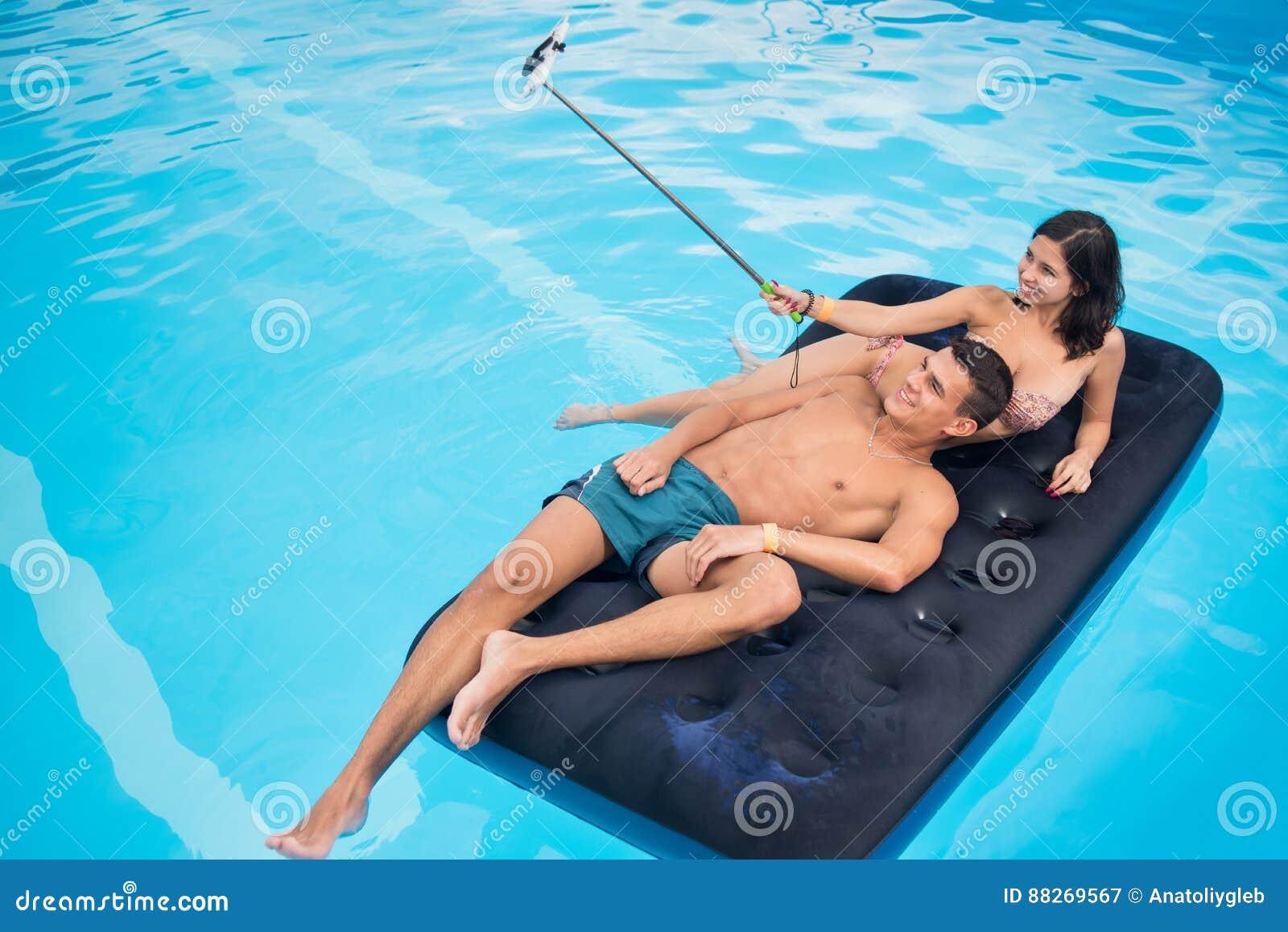 结合漂浮在水池的床垫和拍在电话的selfie照片用selfie棍子他们的暑假