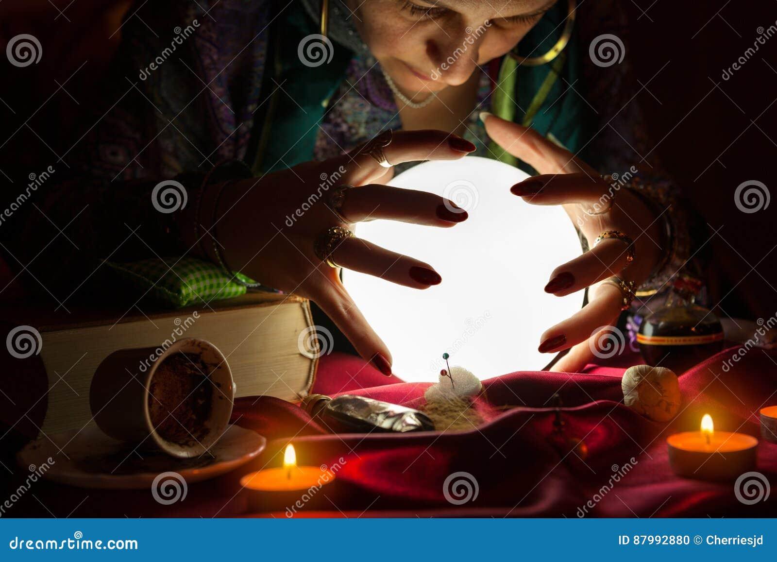吉普赛算命者妇女用她的在水晶球上的手