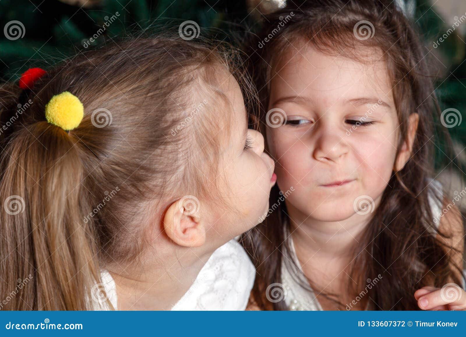 同样年龄谎言的两个逗人喜爱的姐妹在新年树旁边的 一