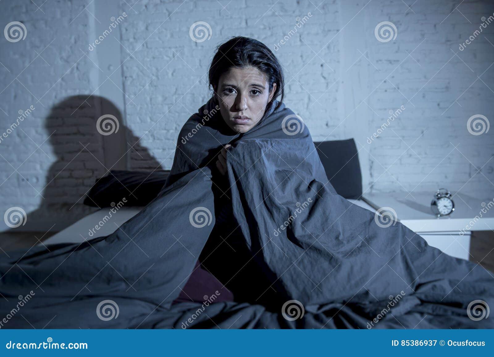 后在床上的西班牙妇女在家卧室在设法的晚上睡觉遭受的失眠