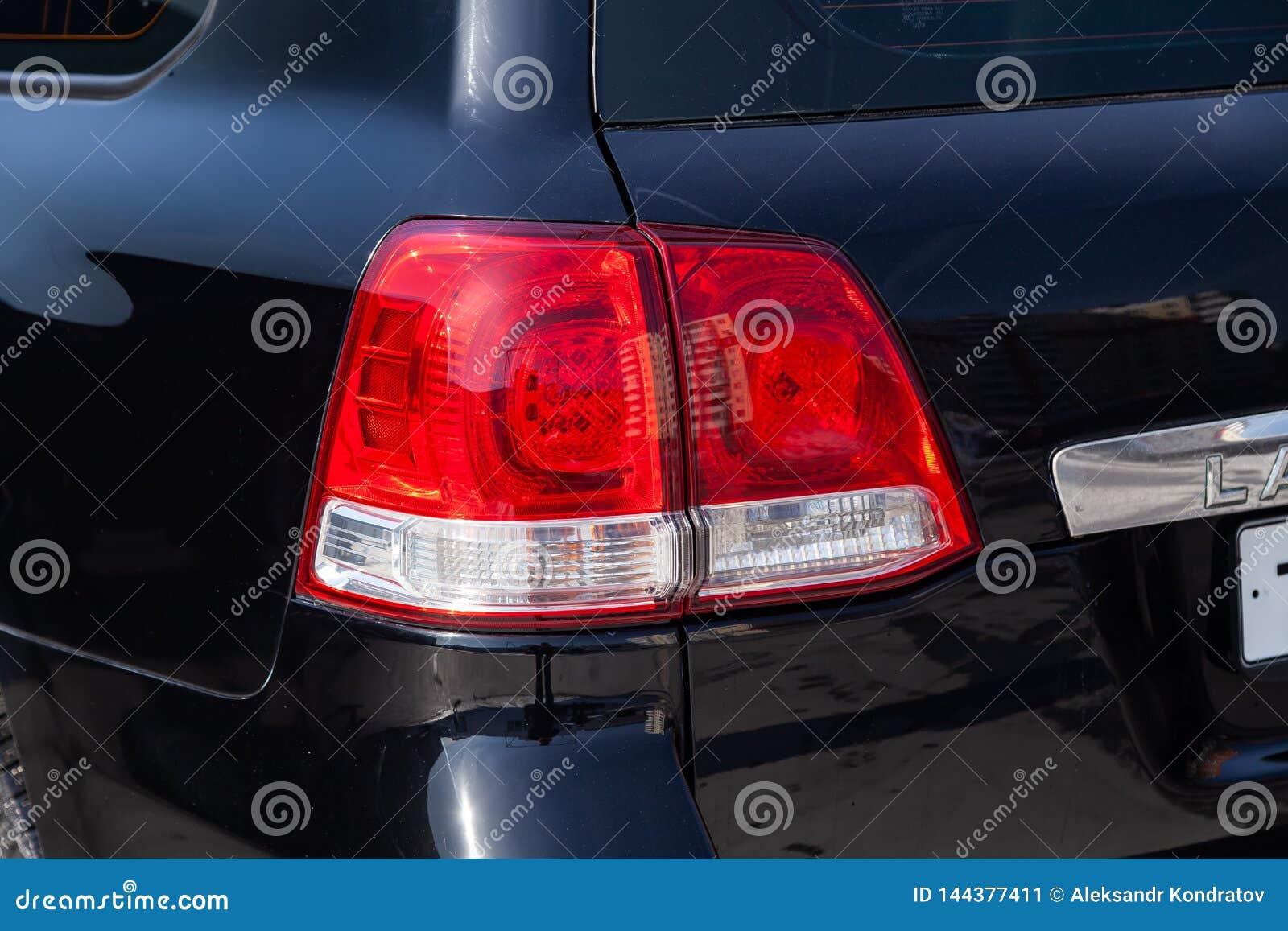 后方尾灯视图在黑色的丰田陆地巡洋舰200在清洗在销售前以后在停车处的一好日子